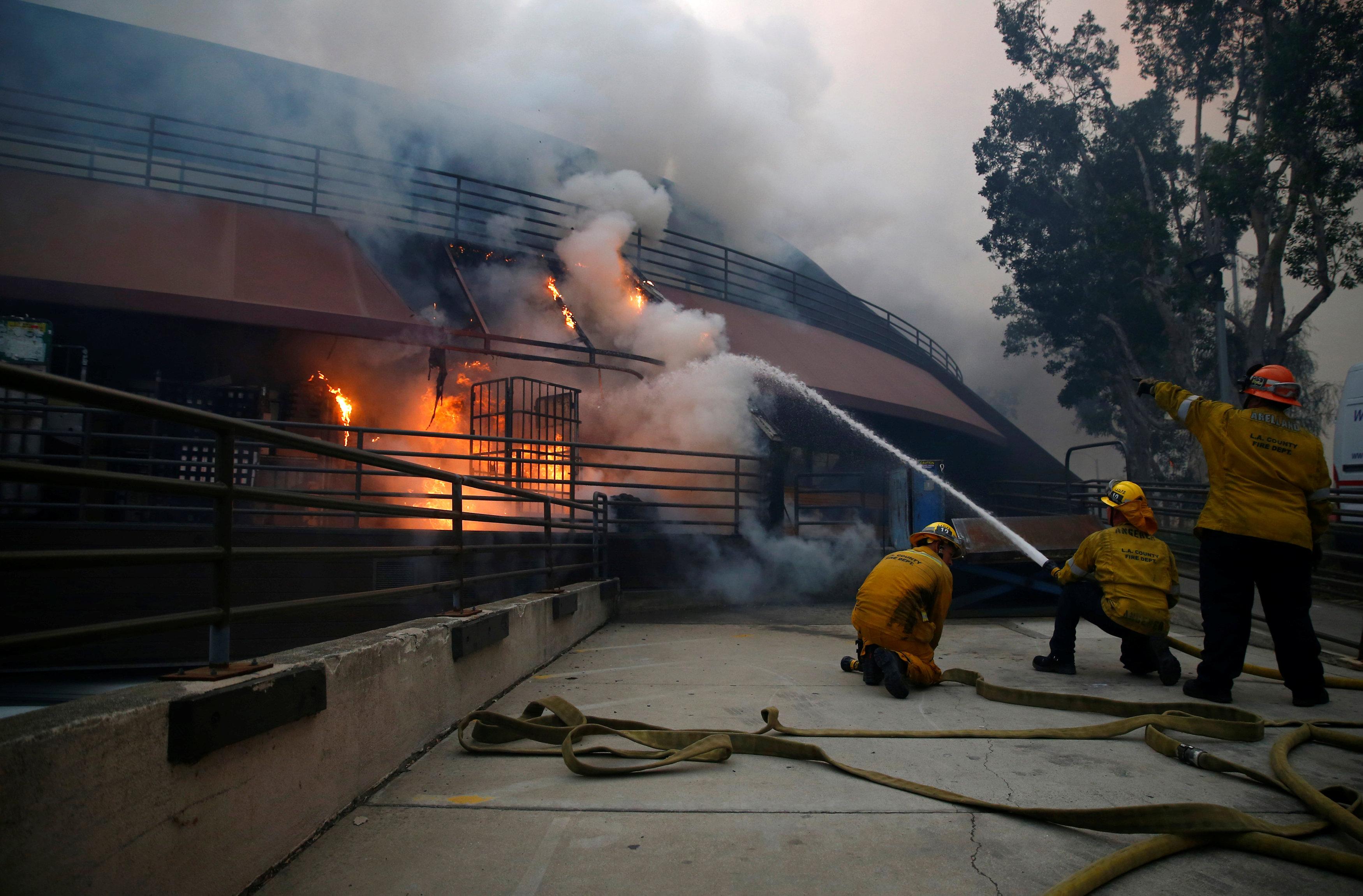 Bomberos luchan contra las llamas en una casa incendiada. REUTERS/Eric Thayer