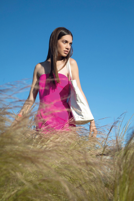 Vestido de paño strapless ($ 10.000, L'Academie Boutique) y bolso de charol ($ 3.460, Mishka).