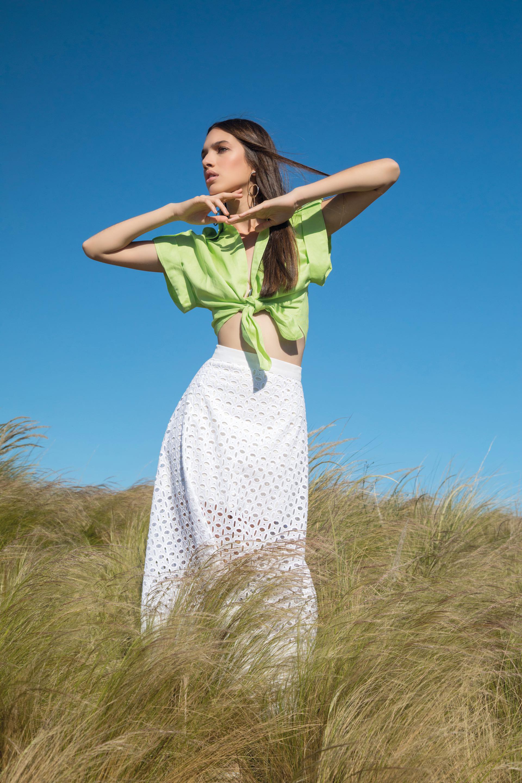 Camisa de lino con lazo y falda midi de broderie (DOT Store), collar semilargo con cadena y dijes y aros con eslabones de argollas irregulares ($ 1.125 y $ 900, Uma).