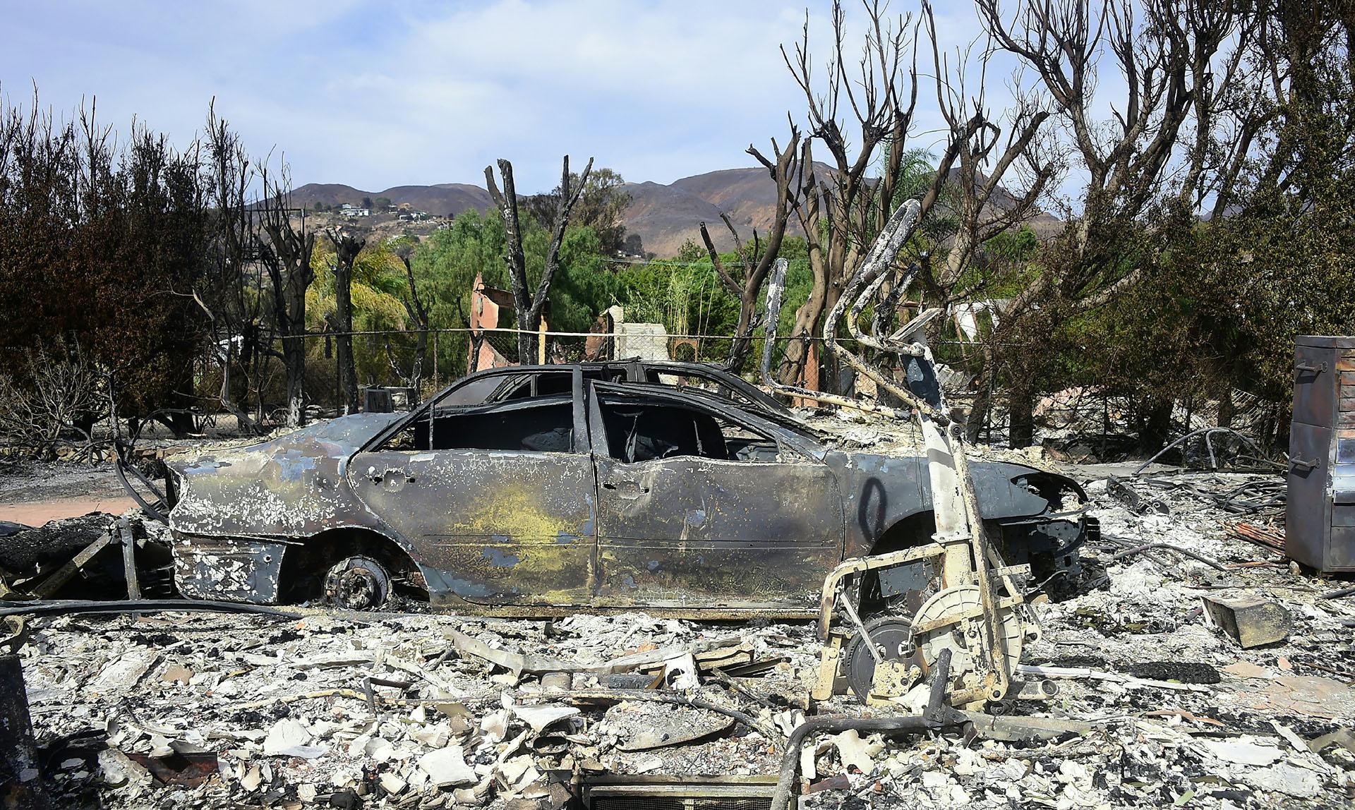 Los restos de una bicicleta de gimnasio son apenas distinguibles entre las cenizas junto a dos vehículos quemados