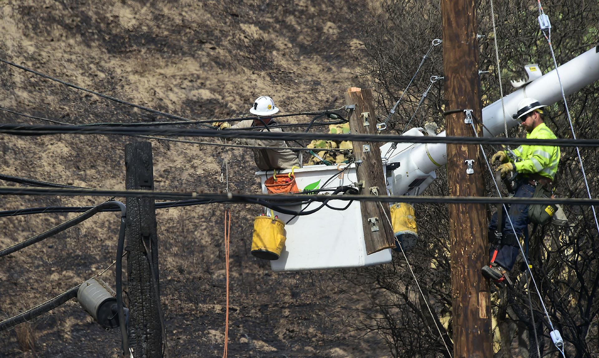 Trabajadores intentan recomponer el tendido eléctrico afectado por el fuego
