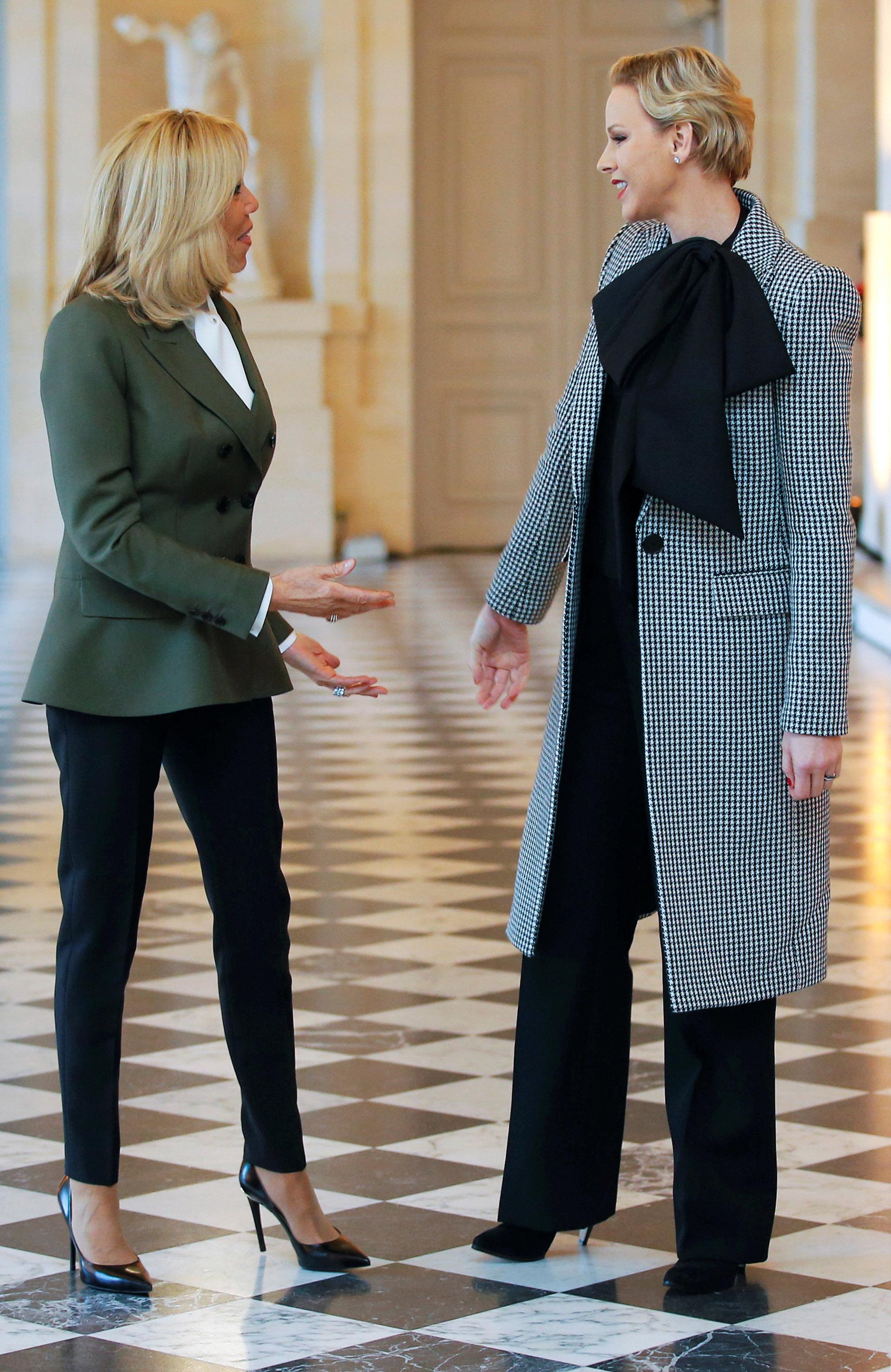 El saludo entre la primera dama francesa, Brigitte Macron, y la princesa Charlene durante un posterior encuentro en el Palacio de Versalles