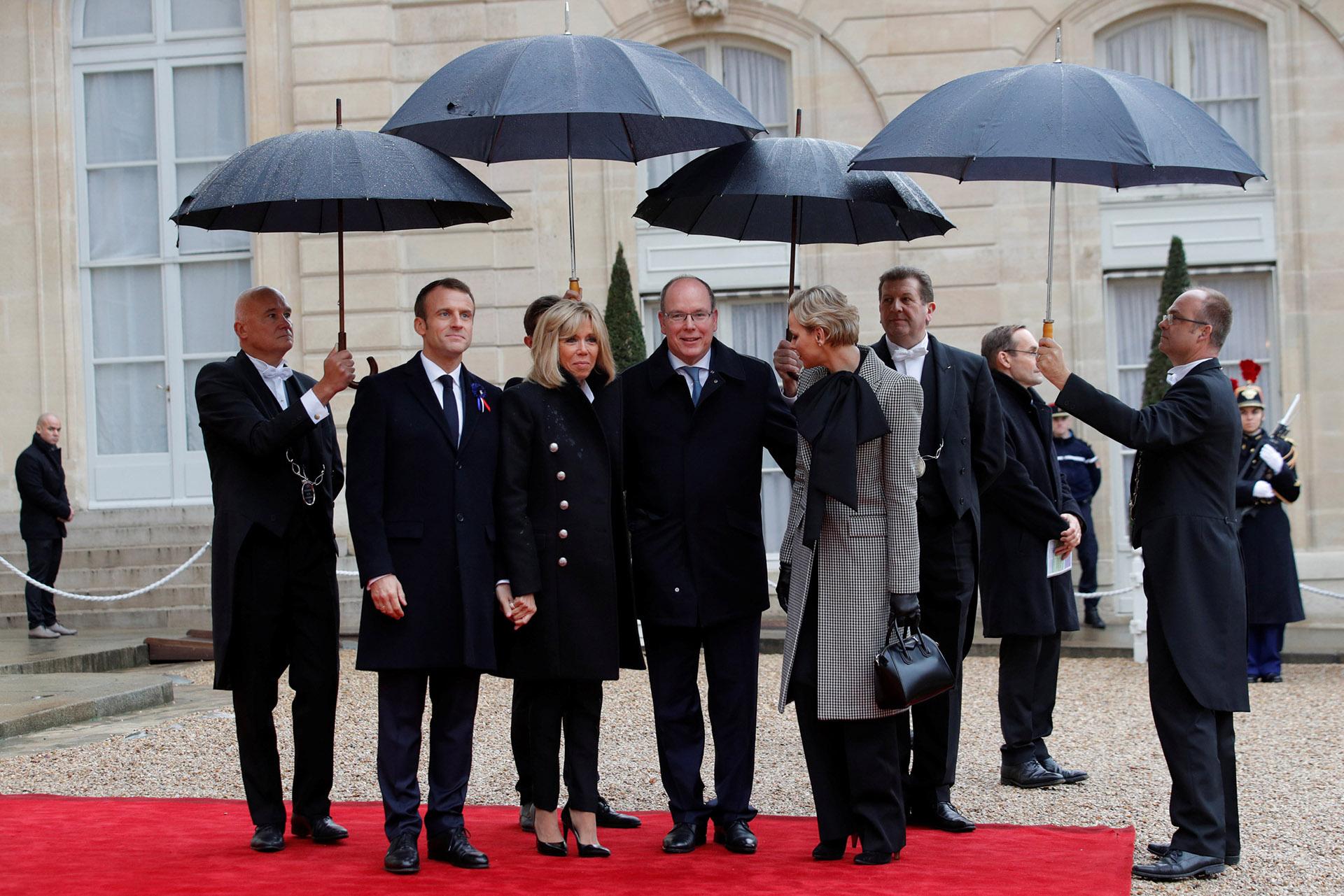 Ambos matrimonios fueron cubiertos con paraguas negros de la copiosa lluvia que cayó sobre París