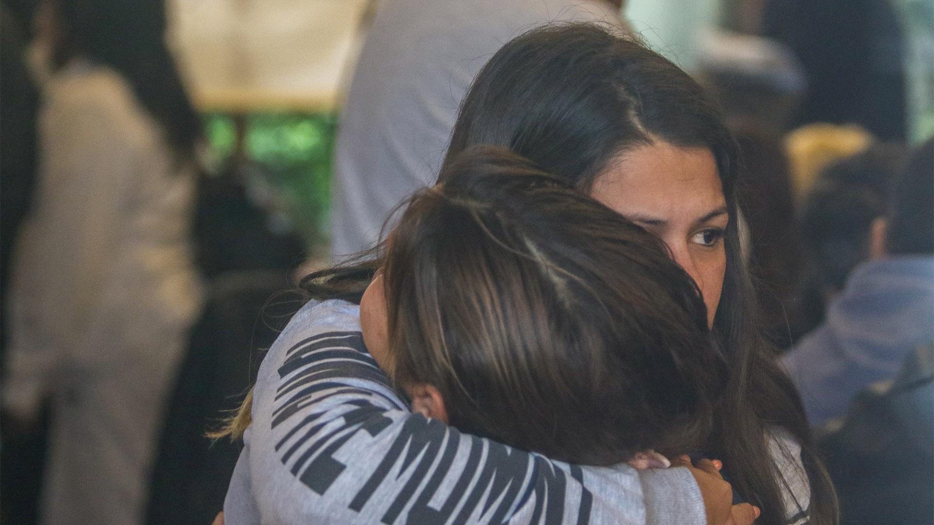 Un grupo de familiares se abraza en el lobby del hotel (Christian Heit)
