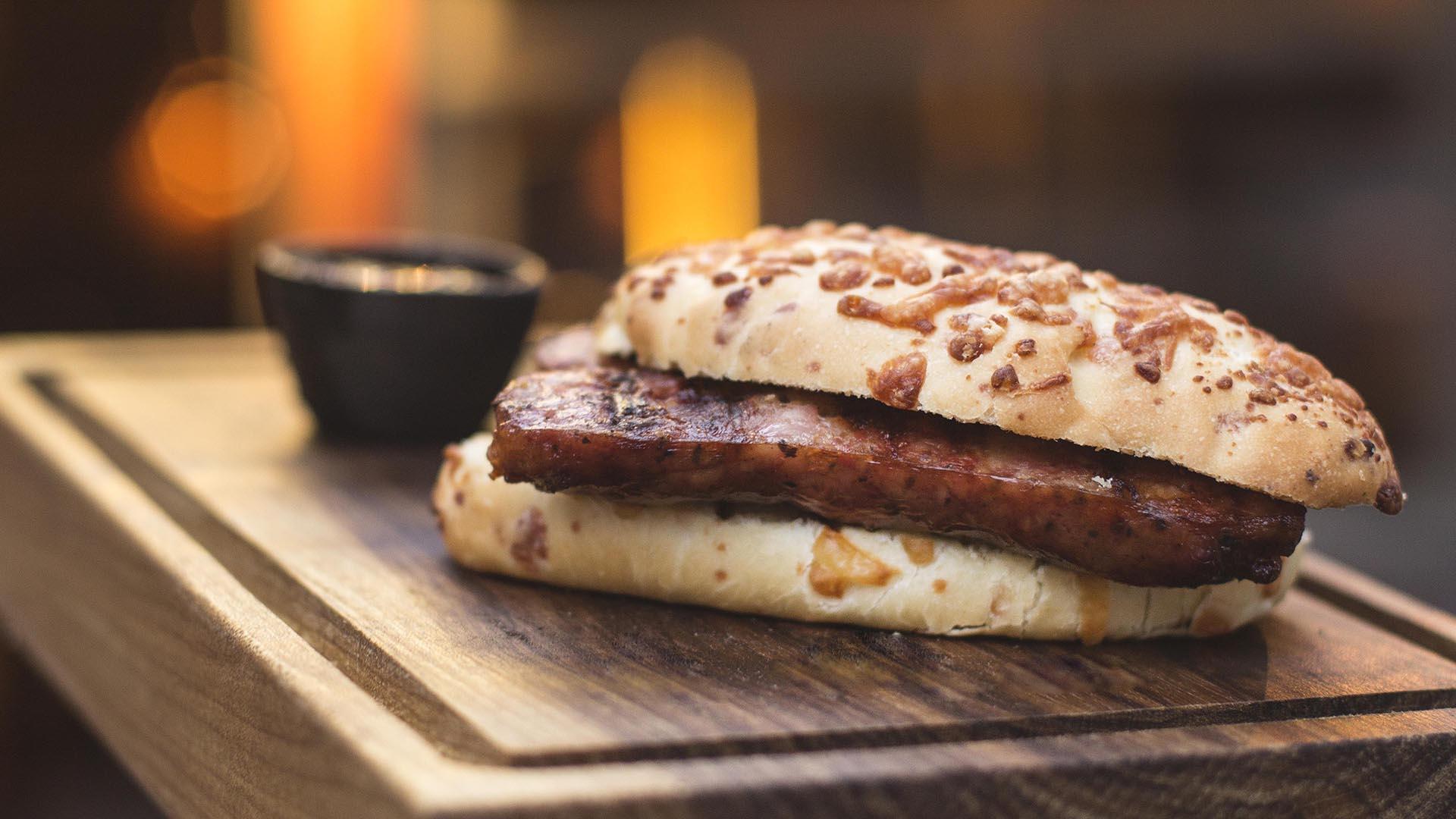Es un sándwich de chorizo casero en pan de queso con dip de salsa criolla o chimichurri