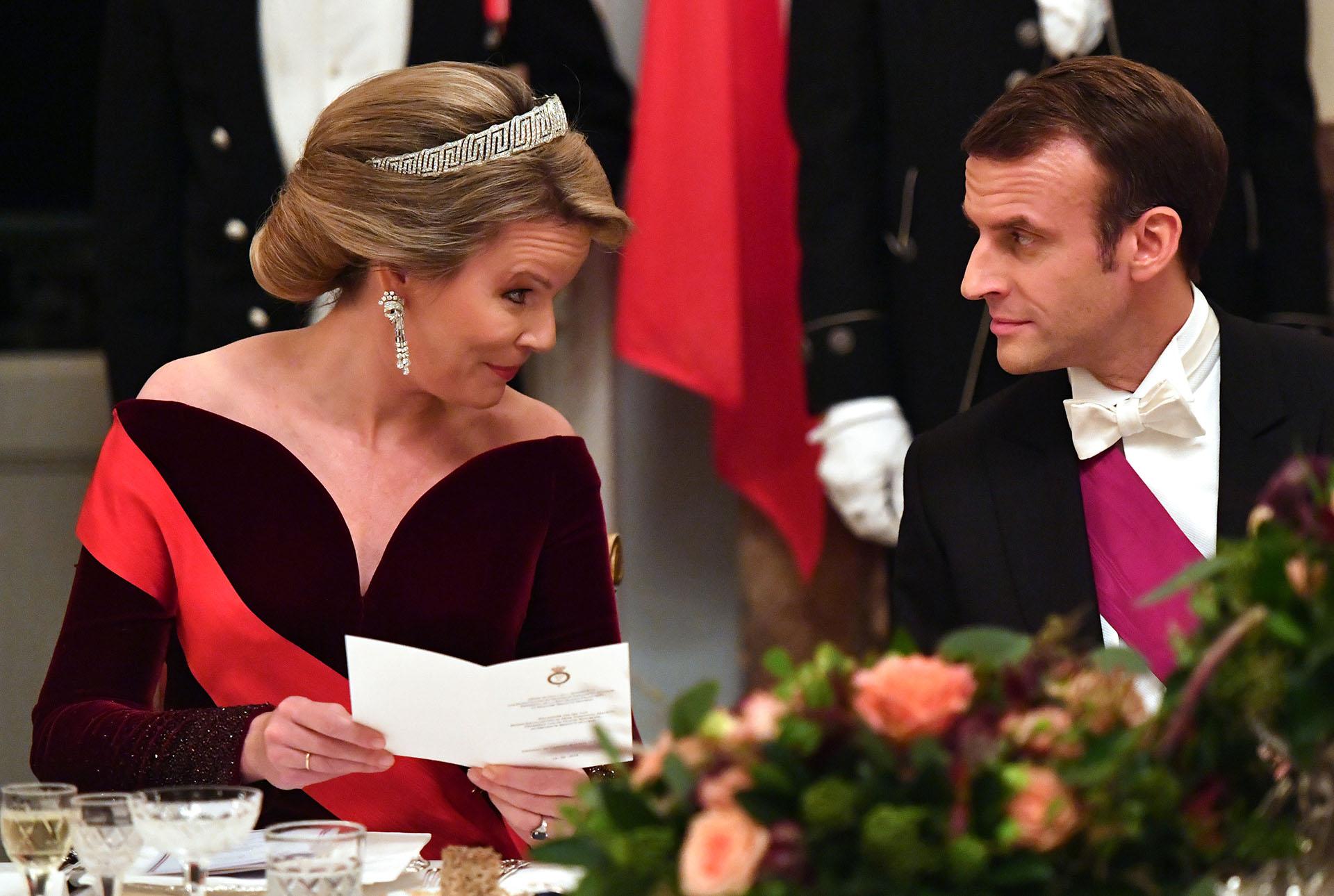 La reina Mathilde conversa con el presidente francés, Emmanuel Macron, en la mesa principal