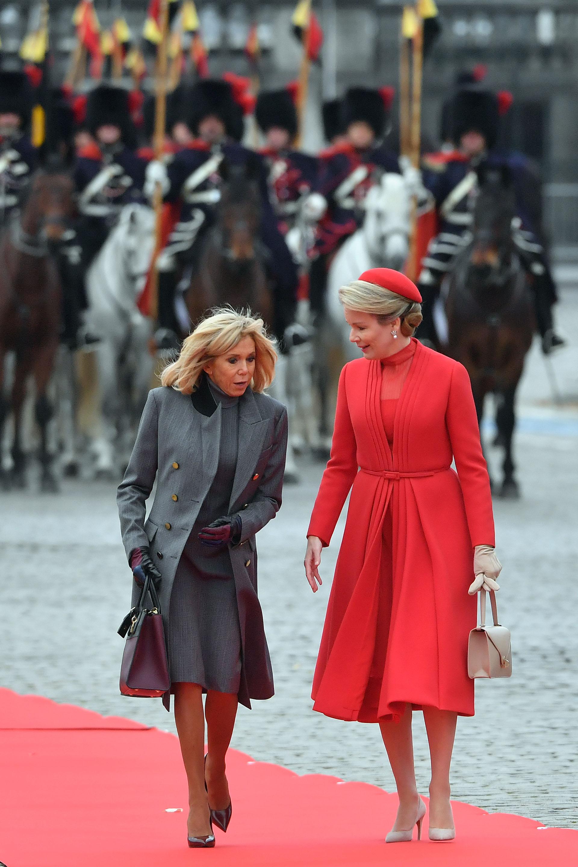 Brigitte Macron se decantó por el color gris oscuro, luciendo un vestido y un tapado con botones dorados