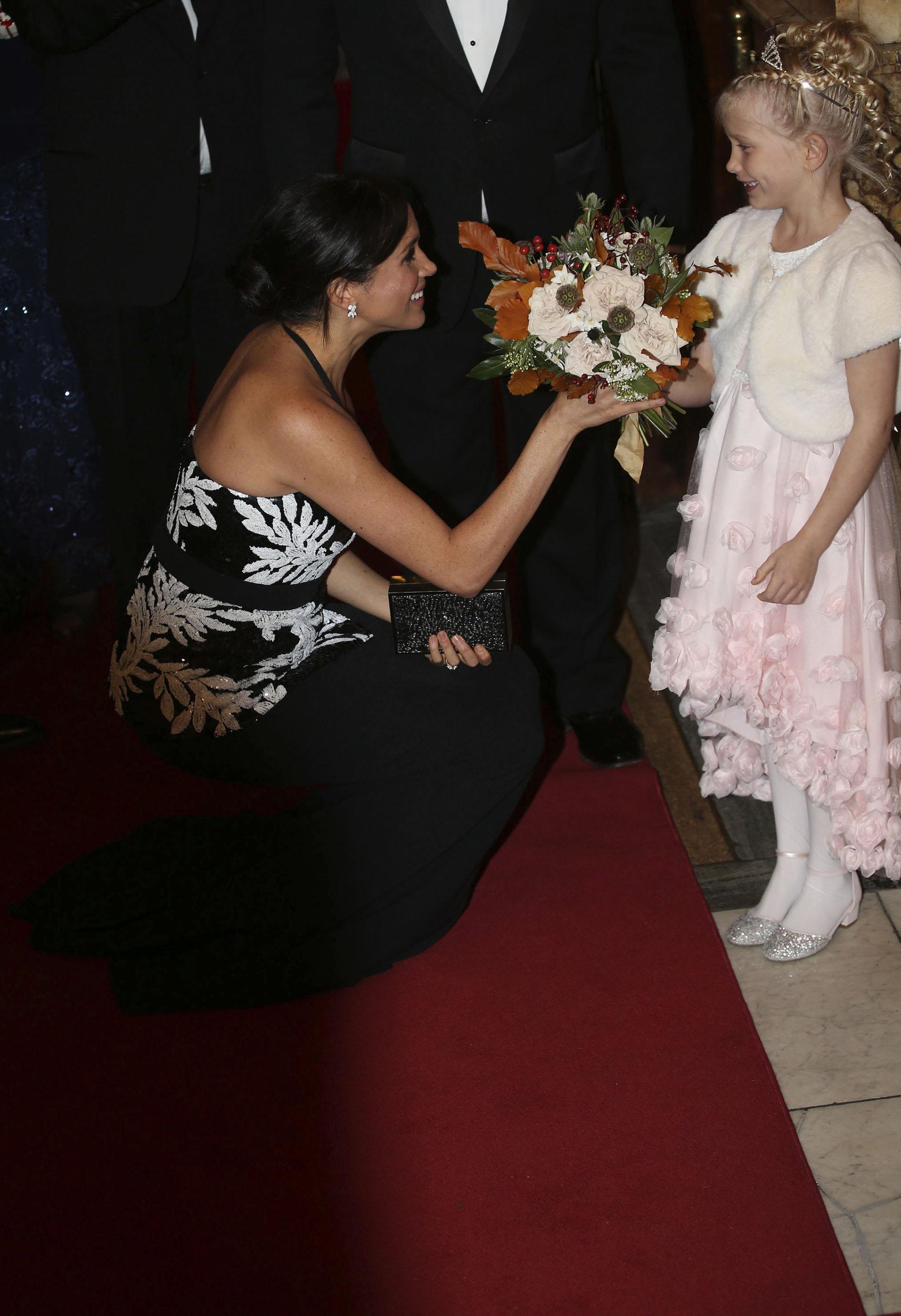 Meghan recibió amablemente un ramo de flores, que le obsequió una niña, y se agachó a saludarla y conversar con ella
