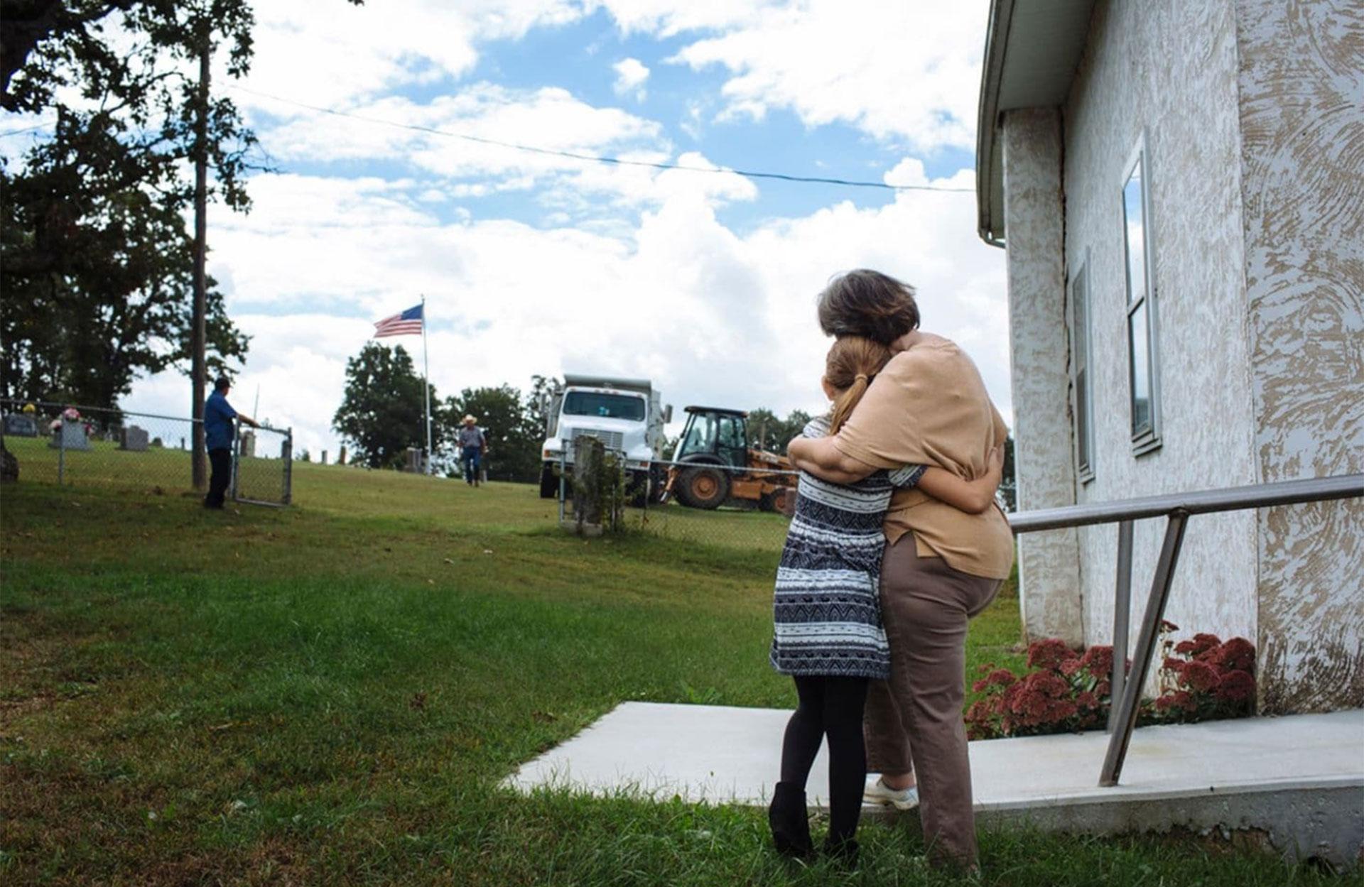Raeleigh y su bisabuela materna, Patsy May, de 65 años, se consuelan mientras se cava una tumba antes del funeral de Raleigh. Había solicitado ser enterrado bajo el asta de la bandera en el cementerio detrás de su iglesia en Hartville, Missouri (Angus Mordant/The Washington Post)
