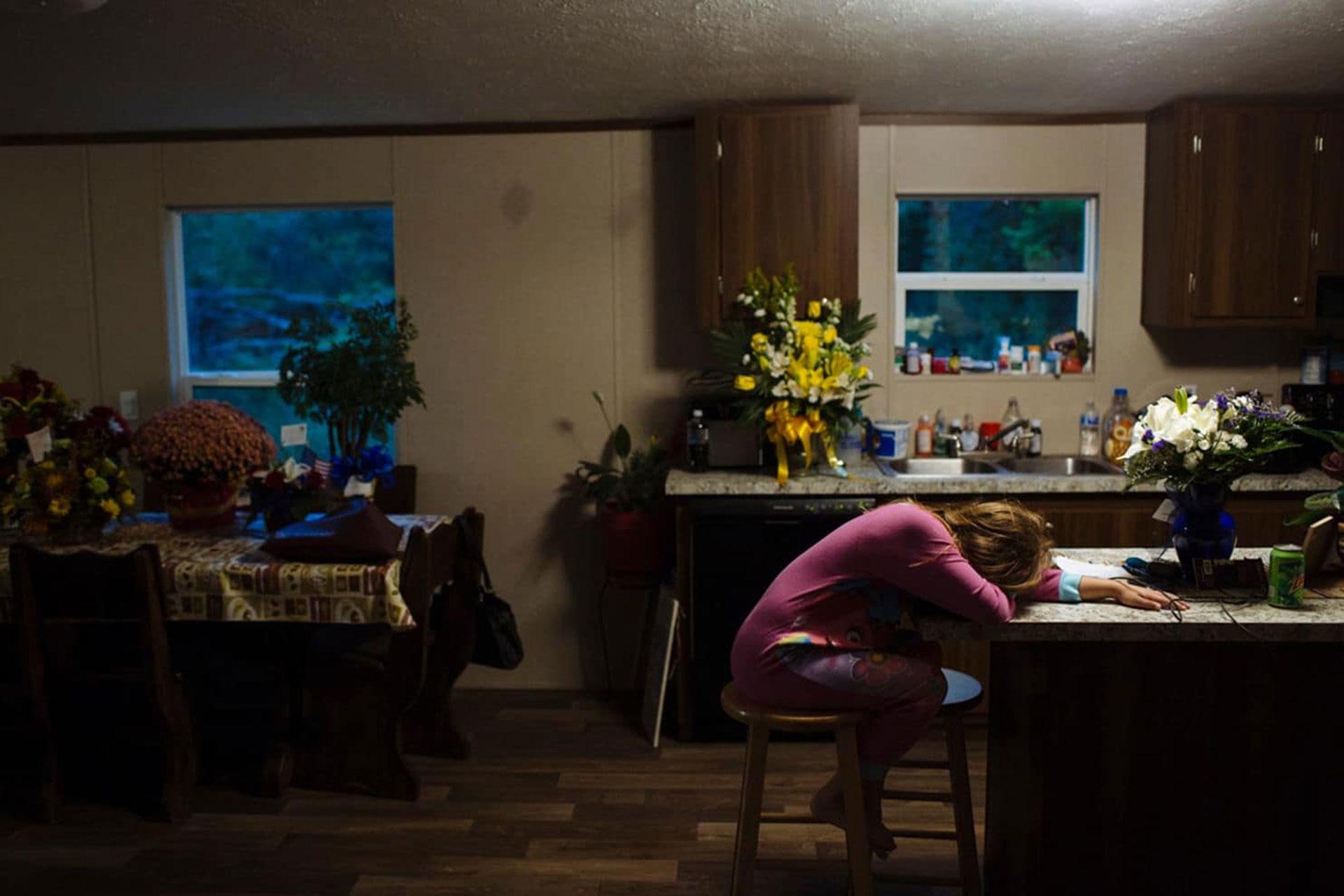 Raeleigh apoya la cabeza en el mostrador de la cocina de su bisabuela la mañana después del funeral de su bisabuelo. Temía regresar a la escuela tras tomarse varios días de descanso por la muerte (Angus Mordant/The Washington Post)