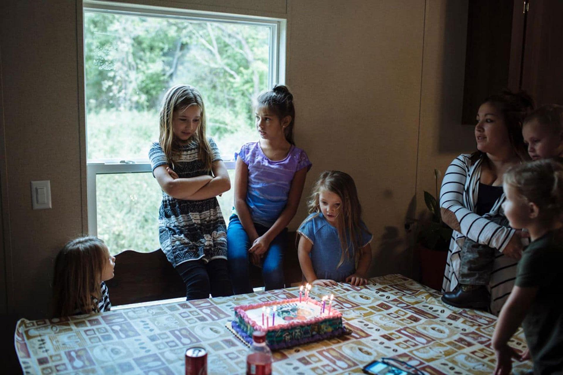 Raeleigh, rodeada de los otros bisnietos y el resto de la familia, en su noveno cumpleaños. Su familia no hizo planes formales de cumpleaños porque su bisabuelo estaba gravemente enfermo. Su muerte tres días antes hizo que la celebración fuera agridulce (Angus Mordant/The Washington Post)