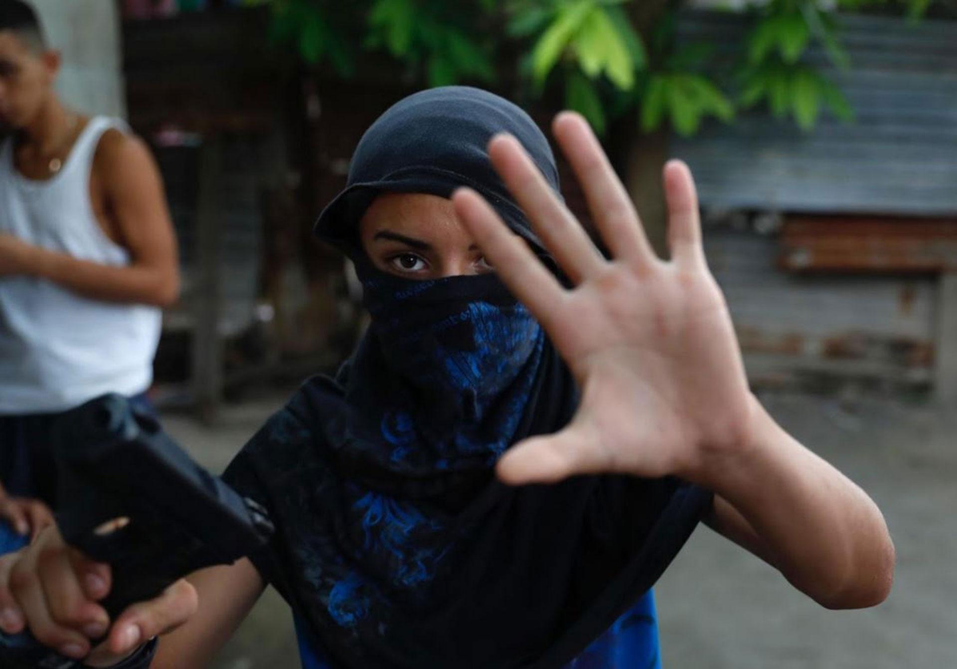 Un joven de la pandilla Barrio 18 muestra un arma