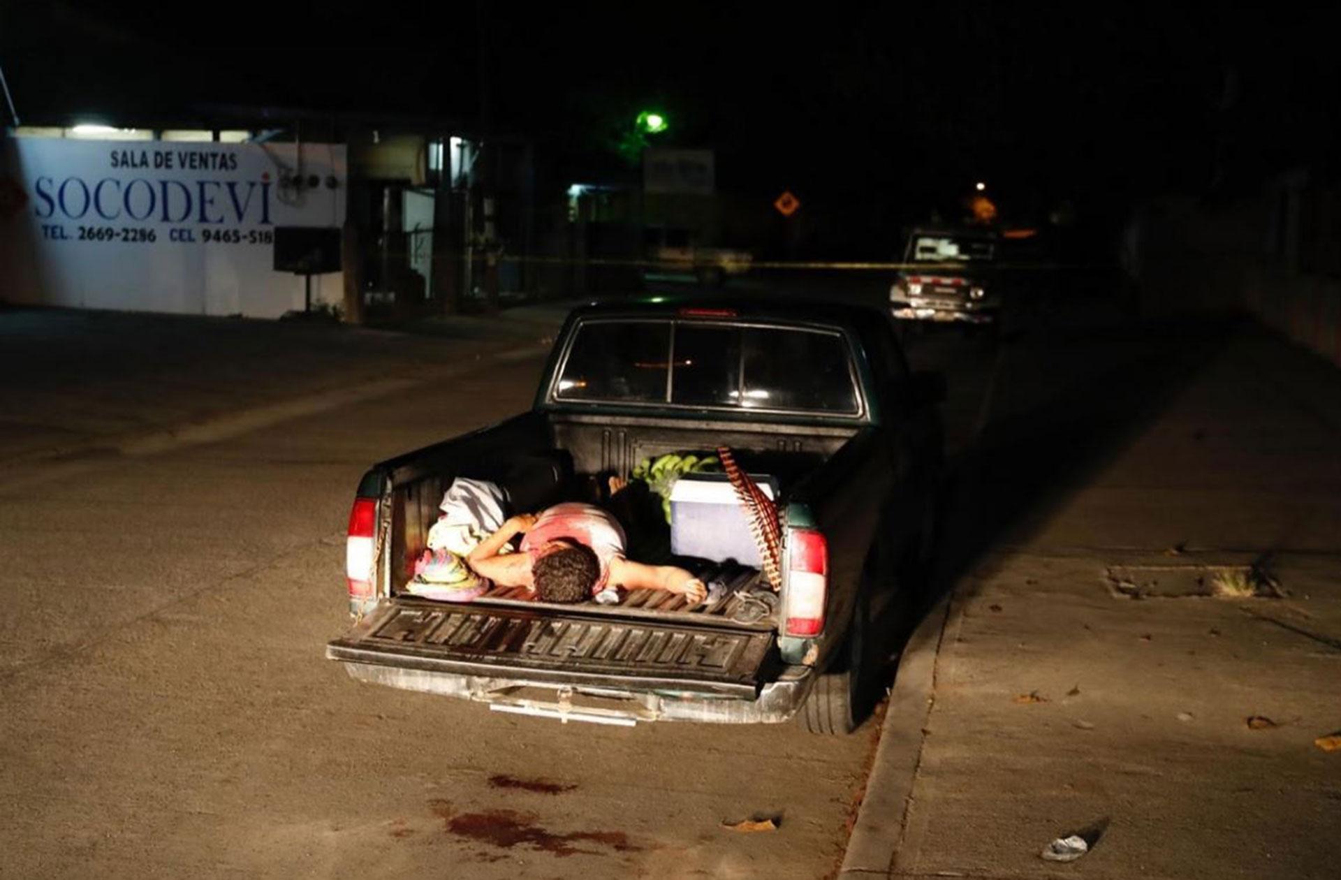 El cuerpo de un hombre muerto por la violencia de pandillas en la caja de un vehículo