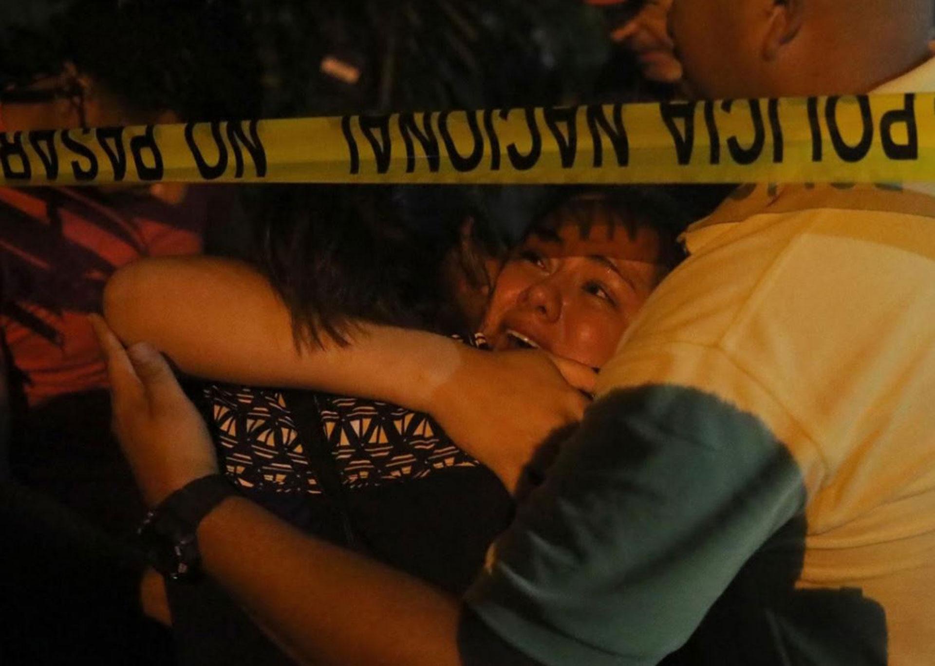 Una mujer llora en la escena del crimen después de que dos hombres fueron asesinados por la violencia entre pandillas