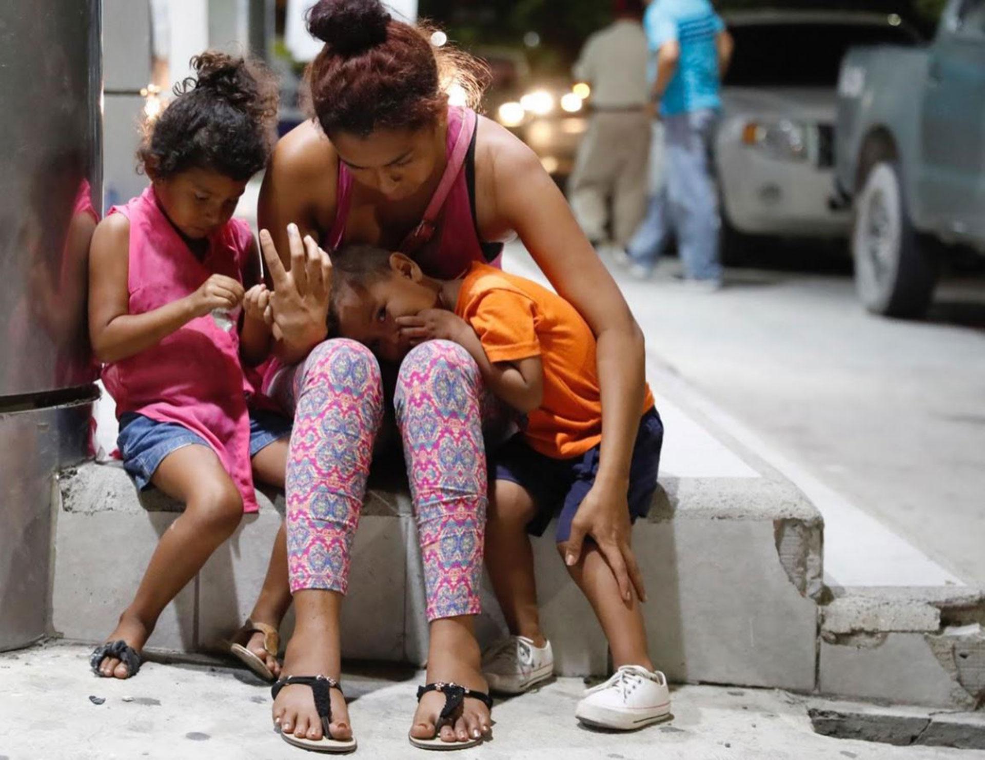Una mujer llora con sus hijos tras la muerte de su marido