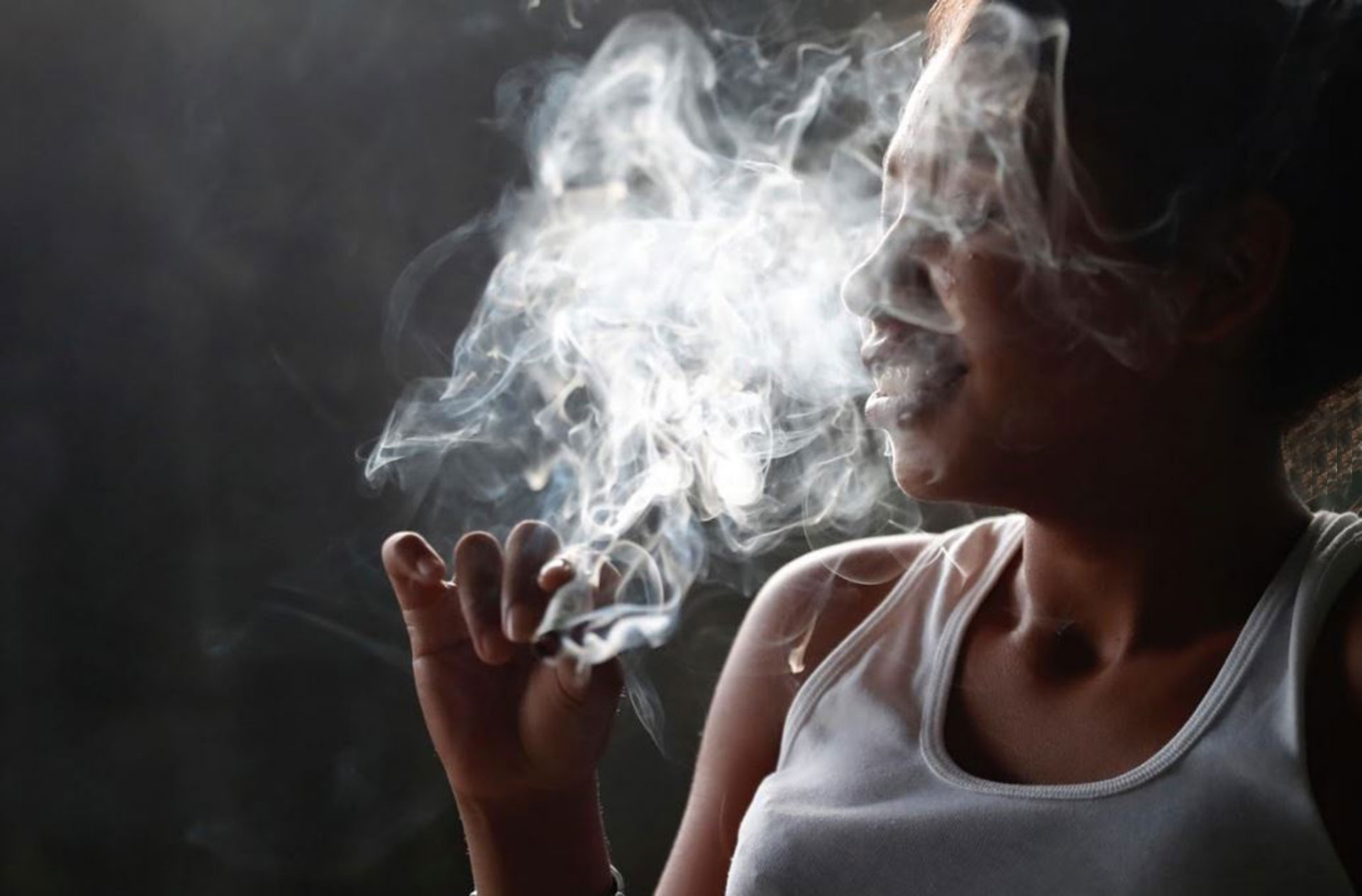 Una mujer fuma marihuana que le compró a los pandilleros