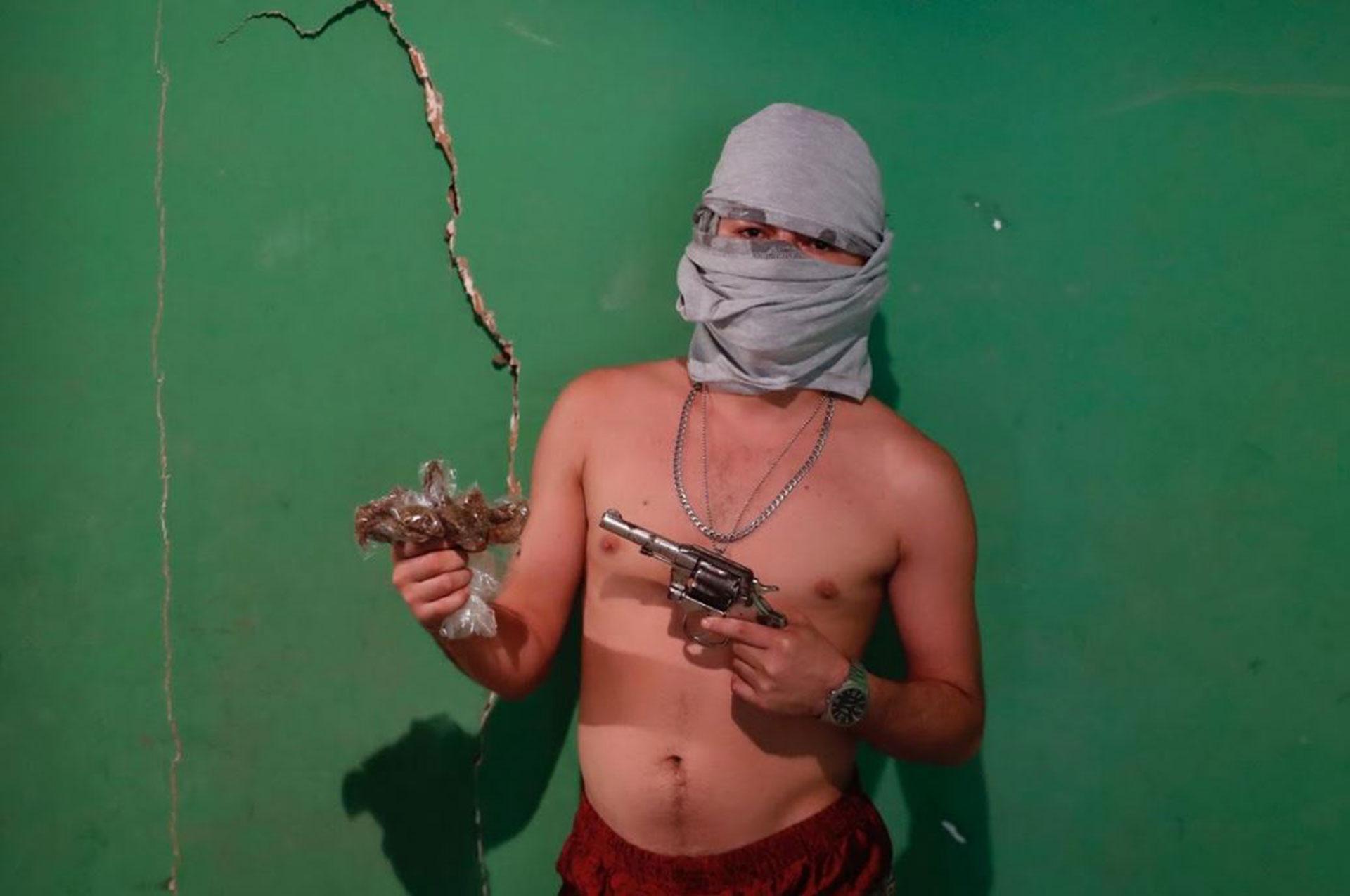 Un pandillero con el rostro cubierto y un arma en una de sus manos