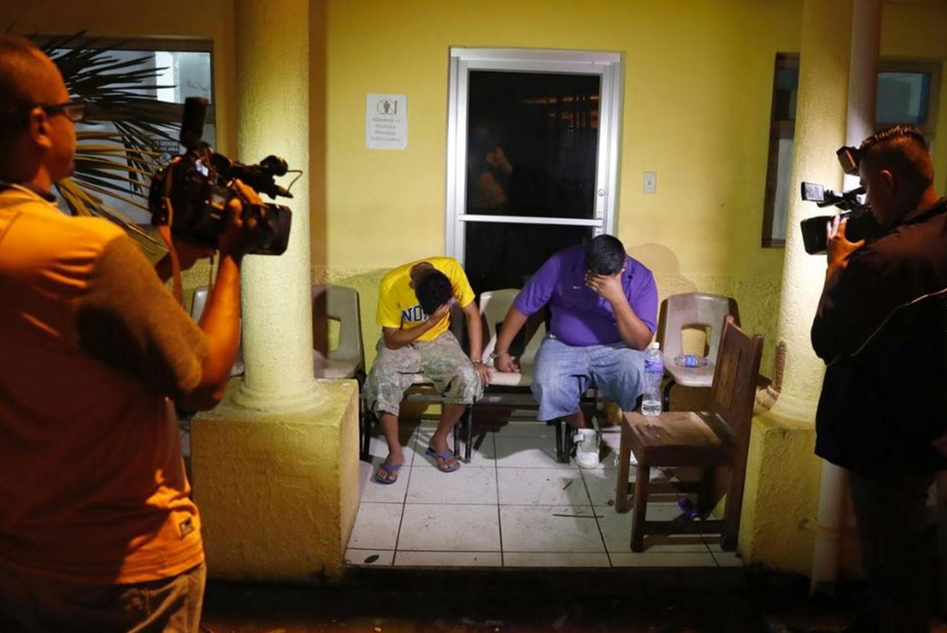 Dos personas se cubren sus rostros mientras son filmados por cámaras
