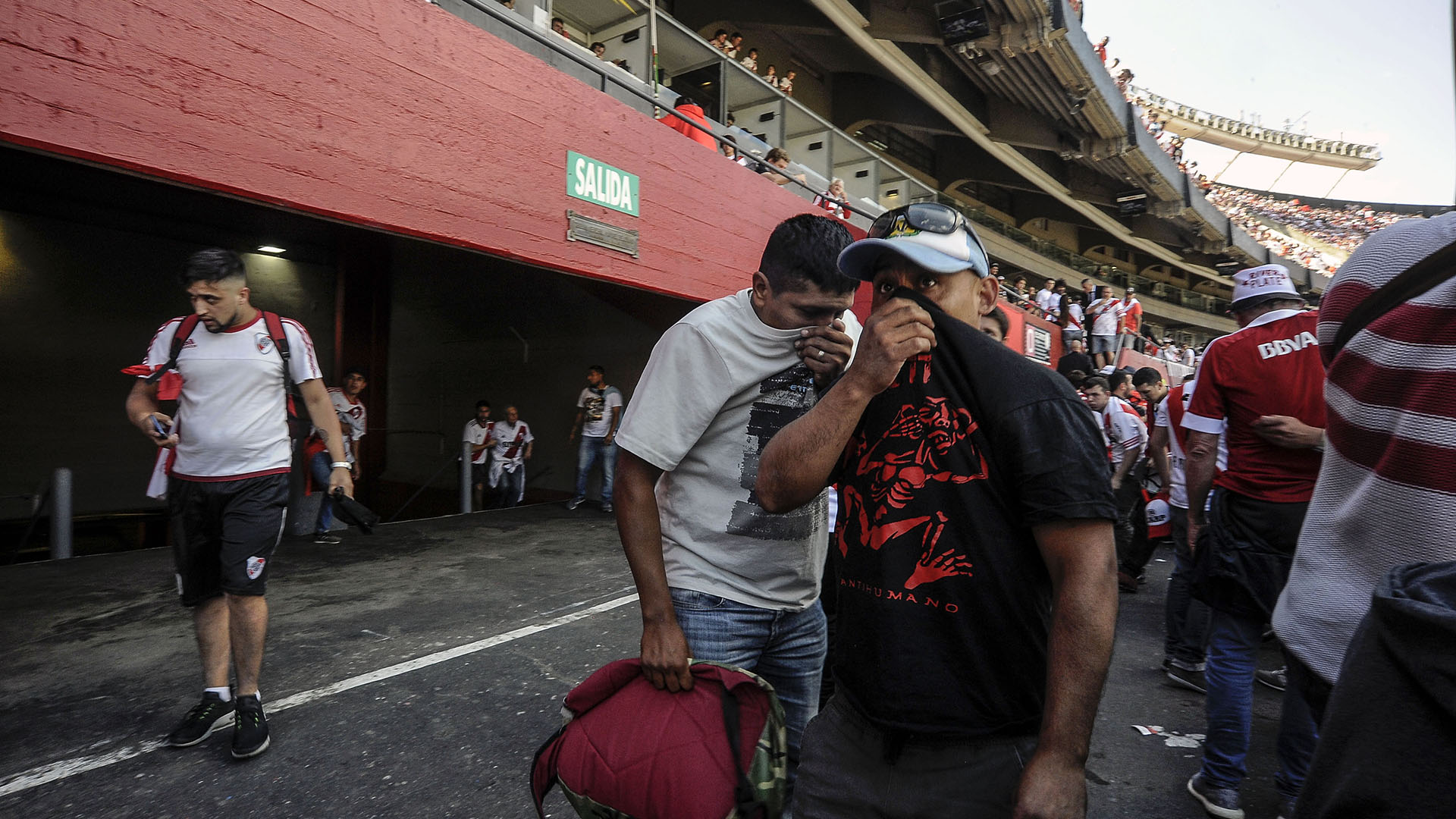Supporters of River Plate cover their faces after being affected by pepper gas sprayed by police outside the Monumental stadium in Buenos Aires, to disperse fans without tickets that tried to enter the arena, before the all-Argentine Copa Libertadores second leg final match between River Plate and Boca Juniors, on November 24, 2018. (Photo by JAVIER GONZALEZ TOLEDO / AFP)