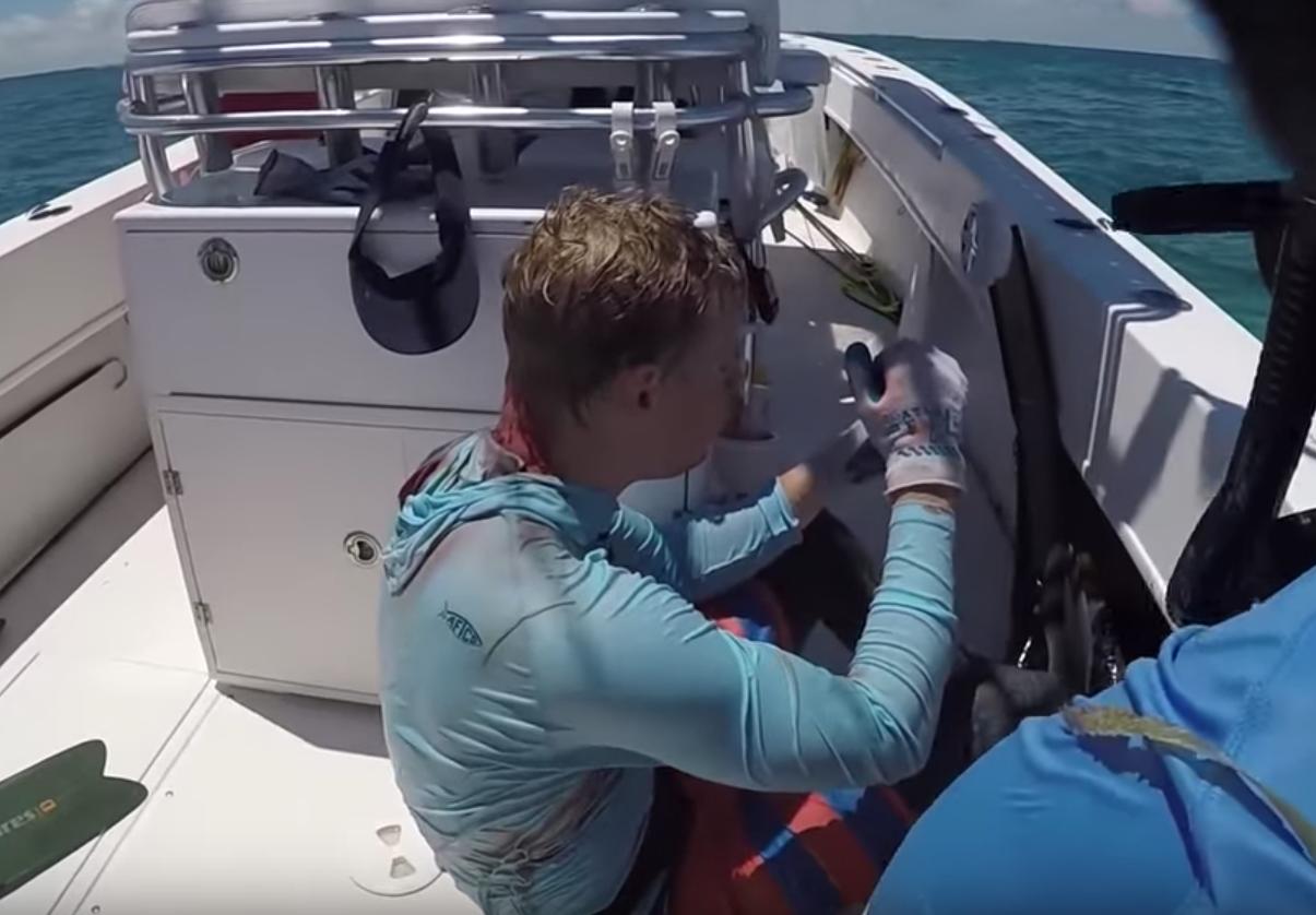 Krause se sienta en la cubierta del bote con sus compañeros de pesca submarina