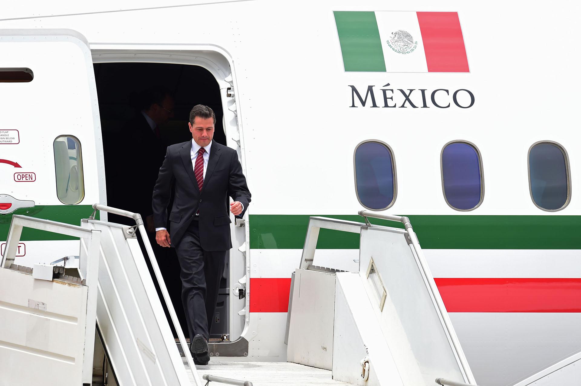 El presidente de México Enrique Peña Nieto, quien mañana traspasará el mando a Manuel López Obrador, baja del avión oficial (AFP)