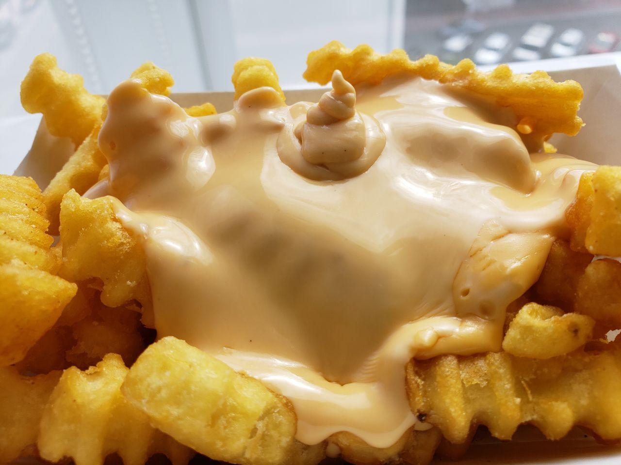 Papas fritas cubiertas con queso cheddar y american cheese: 710 calorías