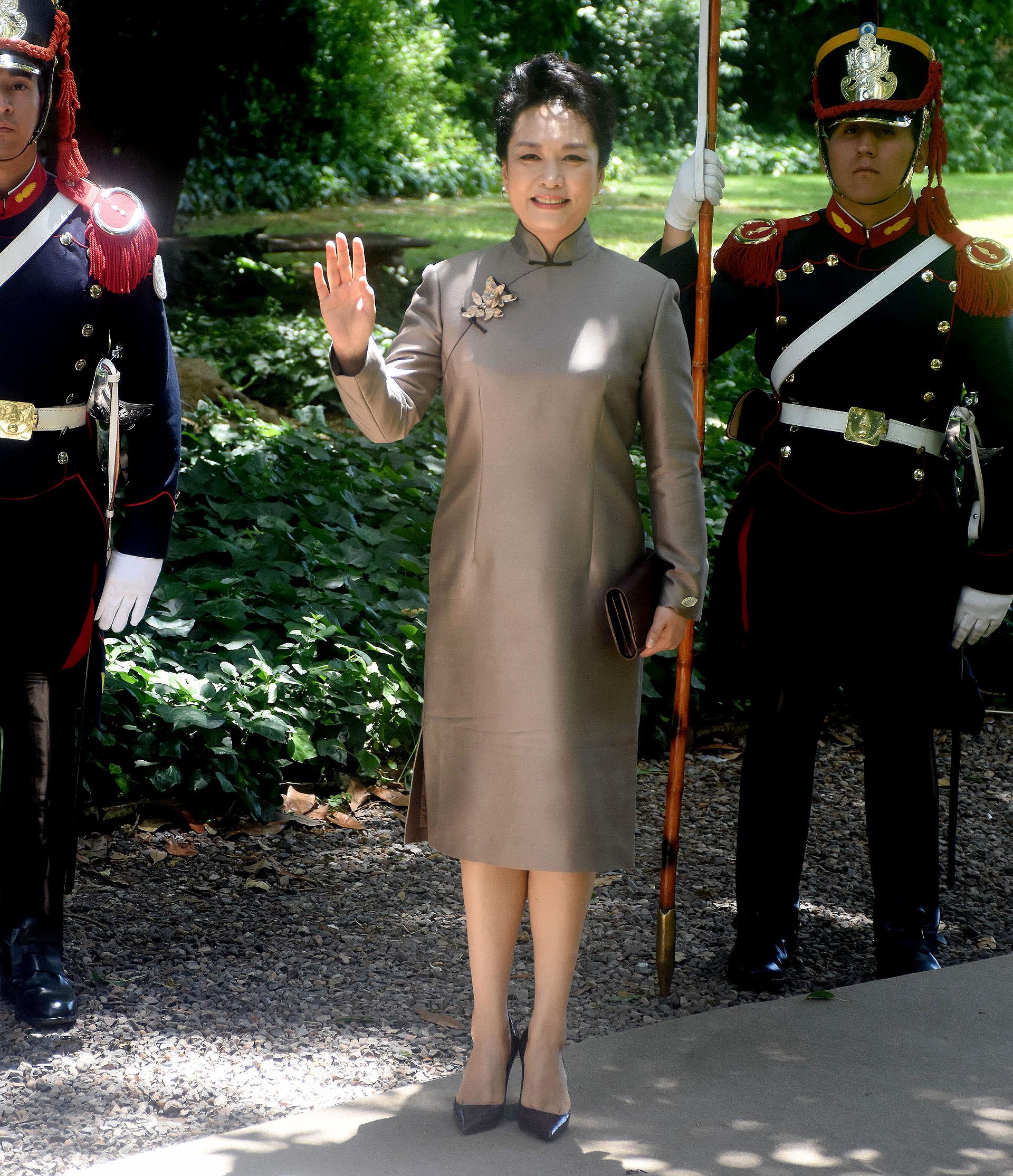 Liyuan Peng, la primera dama de China lució un quipao, la vestimenta tradicional del país engris plomo con detalle de broche-joya sobre el vestido. Lo acompañó con un sobre y stilettos en punta marrón
