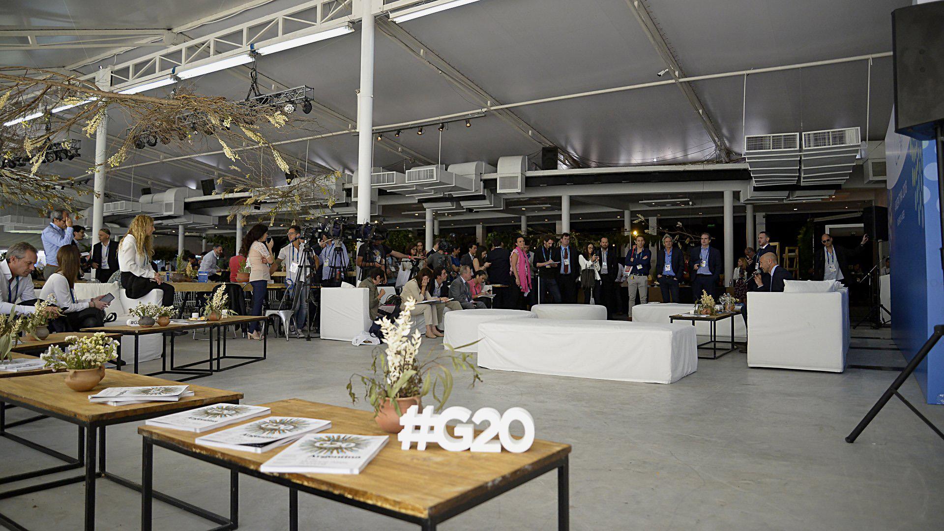 Sobre la mesa, las carpetas y bolsas de nylon con el logotipo del G20 que recibieron los periodistas