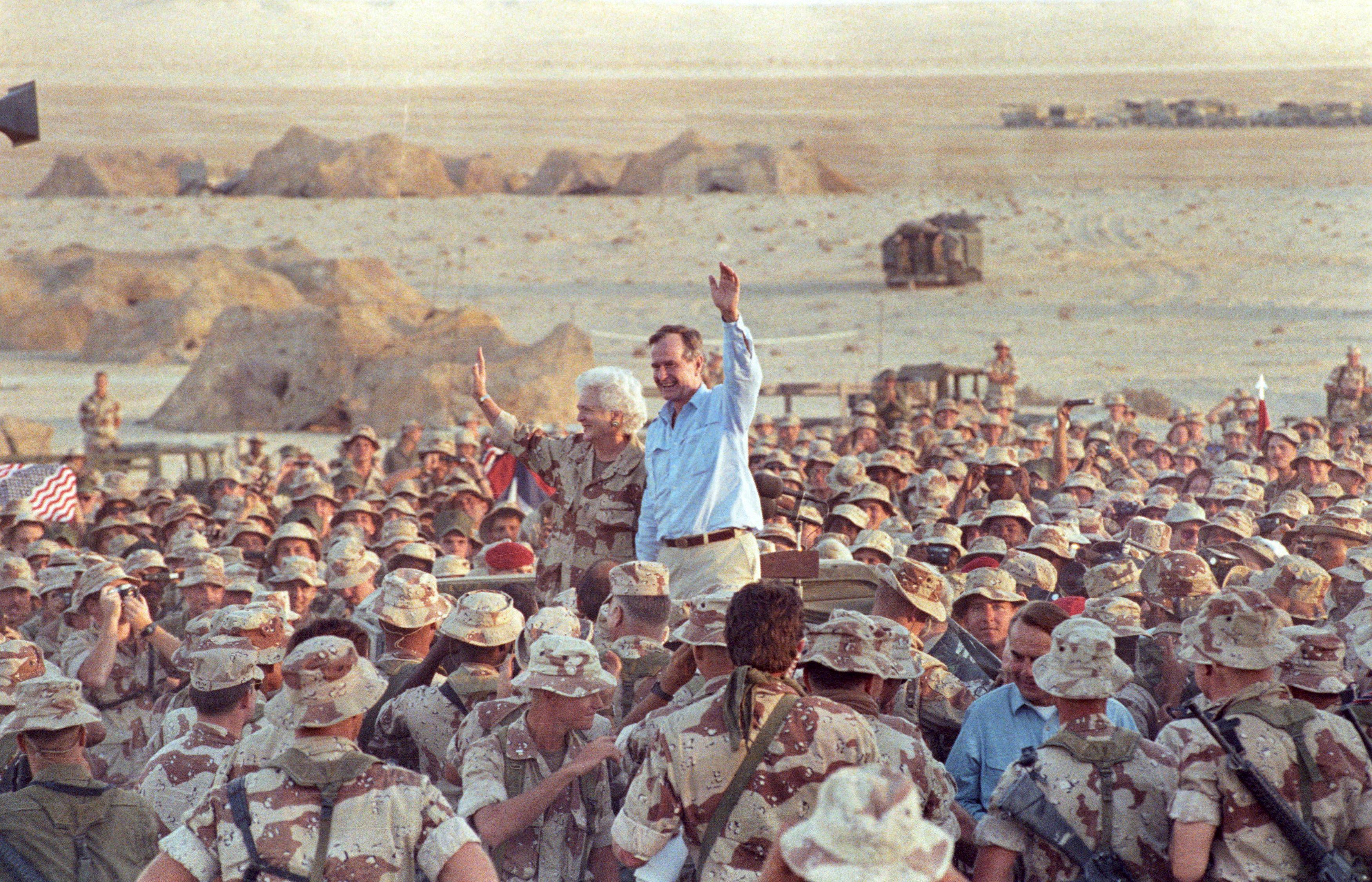 George H. W. Bush waves saluda aMarines and members, luego de las celebraciones del de Día de Acción de Graciasen el desierto saudita el 22 de noviembre de1990. (REUTERS/Rick Wilking)
