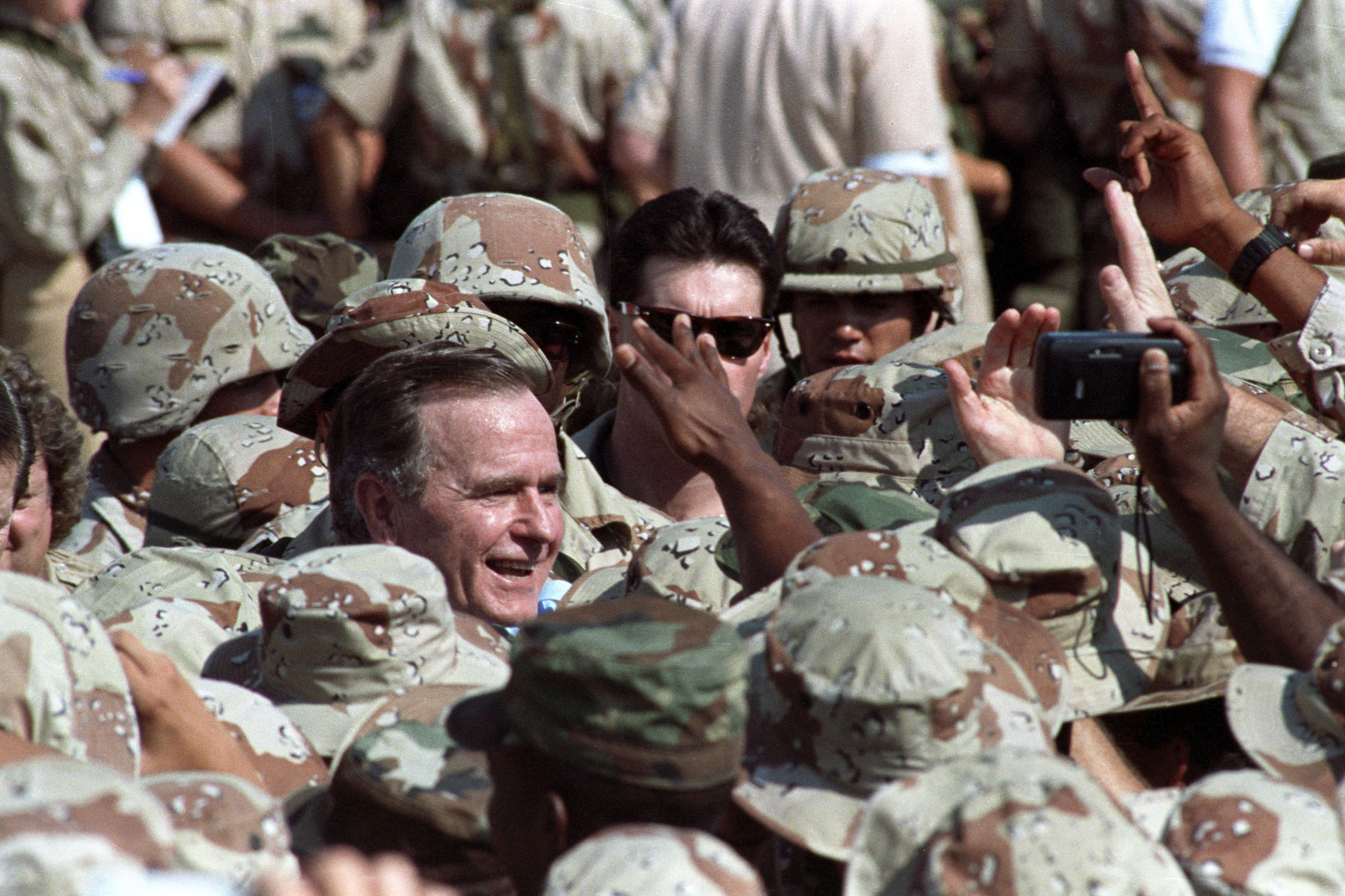George H.W. Bush is surrounded saluda a militares estadounidense en Arabia Saudita el 22 de noviembre 1990. (REUTERS/Terry Bochatey)