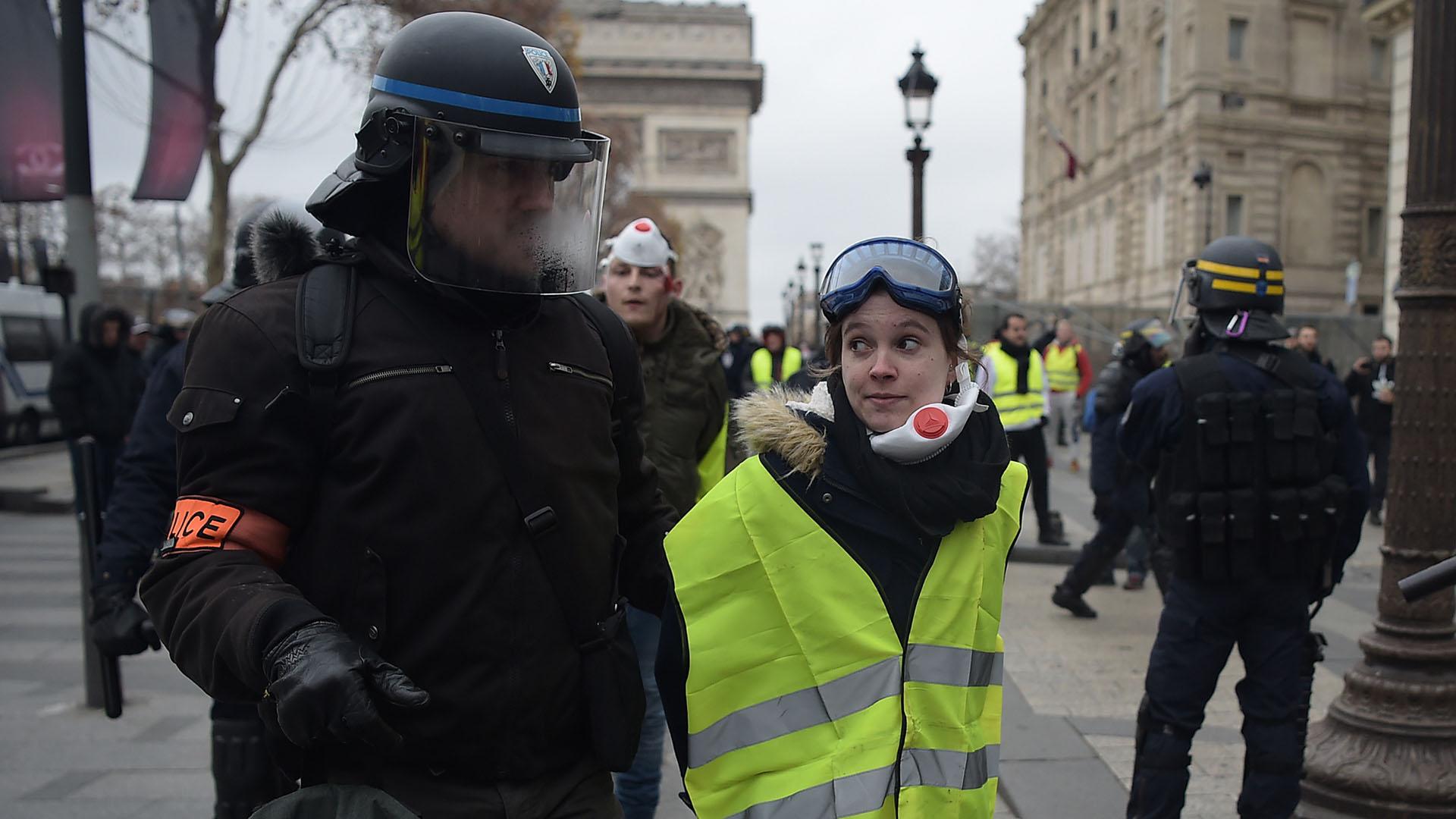 Un policía se lleva detenida a una manifestante (Lucas BARIOULET / AFP)
