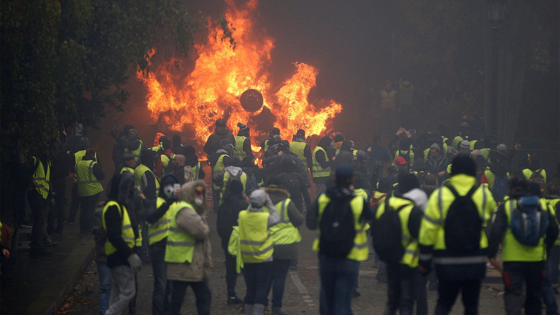 A media mañana, los enfrentamientos proseguían en torno al Arco de Triunfo, en la parte alta de los Campos Elíseos, entre policías y manifestantes, algunos de ellos enmascarados (REUTERS/Stephane Mahe)