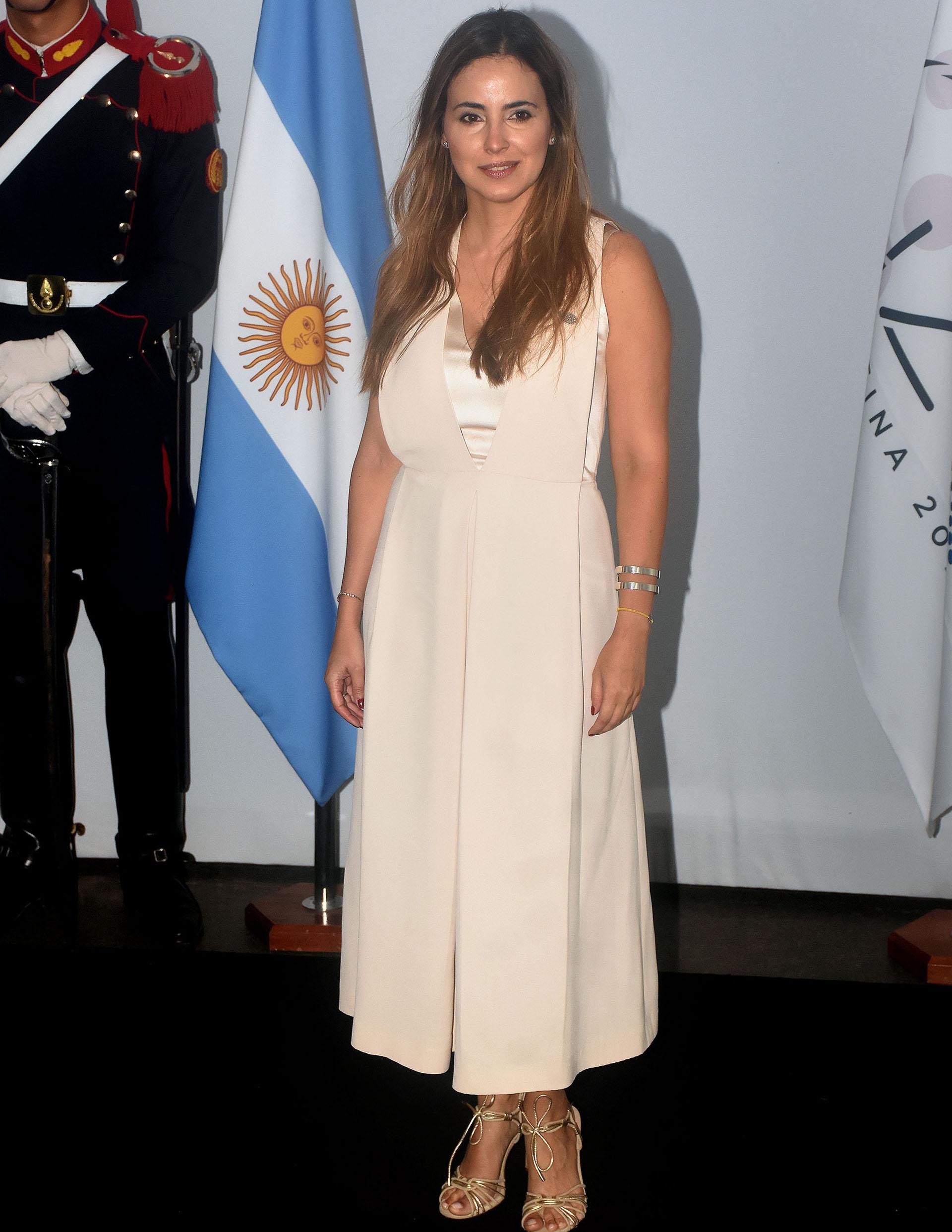 María Gabriela Sigala, del Banco Interamericano de Desarrollo (BID), eligió un vestido sin mangas, gran escote V y combinación de dos géneros: seda natural y raso. Ambos en tonalidades beige. Completó su look con sandalias doradas y esclavas a tono