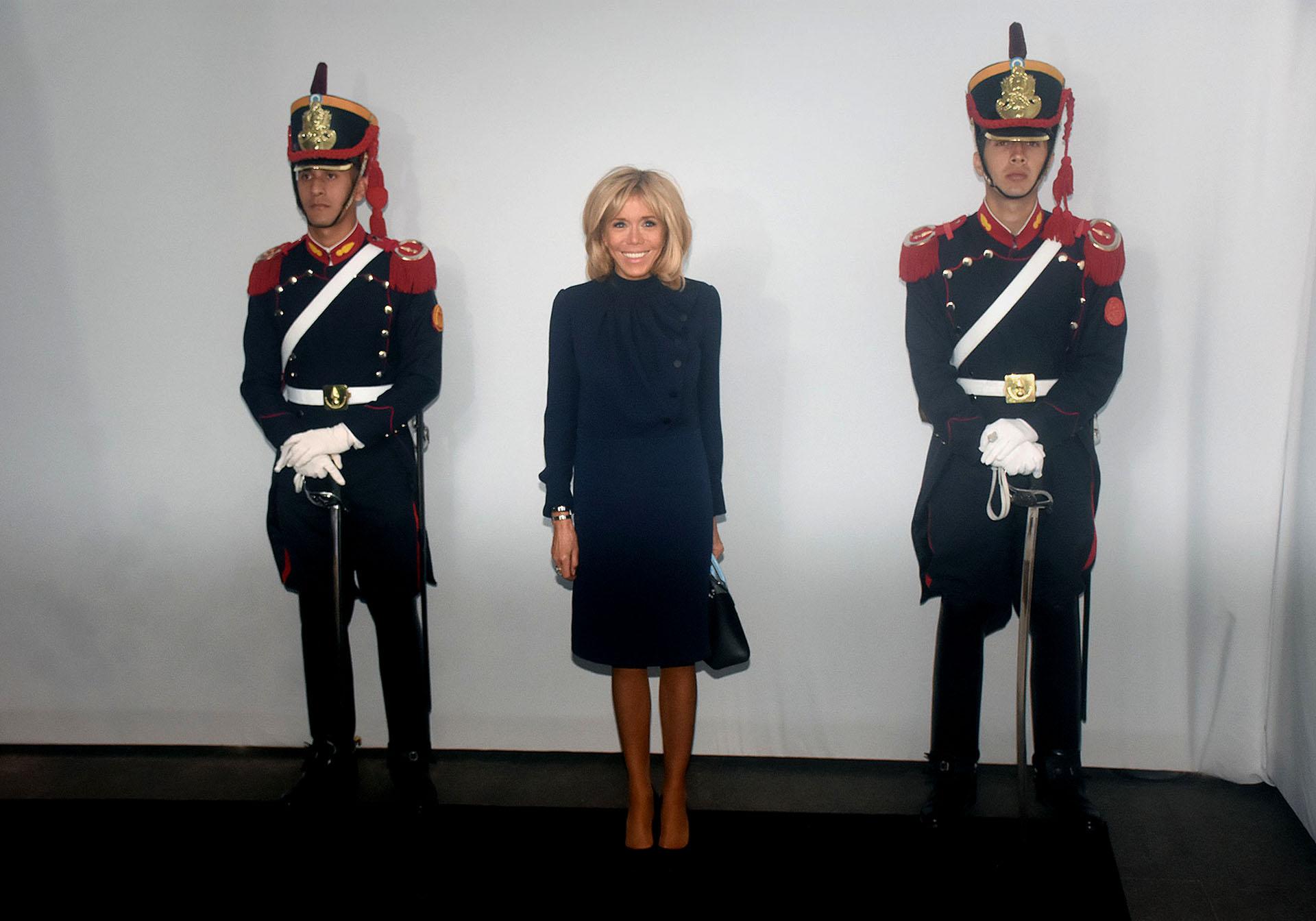 """Brigitte Macron, una de las últimas en llegar al Malba, volvió a elegir un conjunto de dos piezas azul noche -el """"nuevo negro"""" en la moda-. Una blusa con jabot y botones a tono y la falda pencil que tanto caracteriza a la primera dama francesa. Completó su look con una mini bag y zapatos a tono. El beauty look, al igual que siempre, su cabello bob y make up sobrio"""