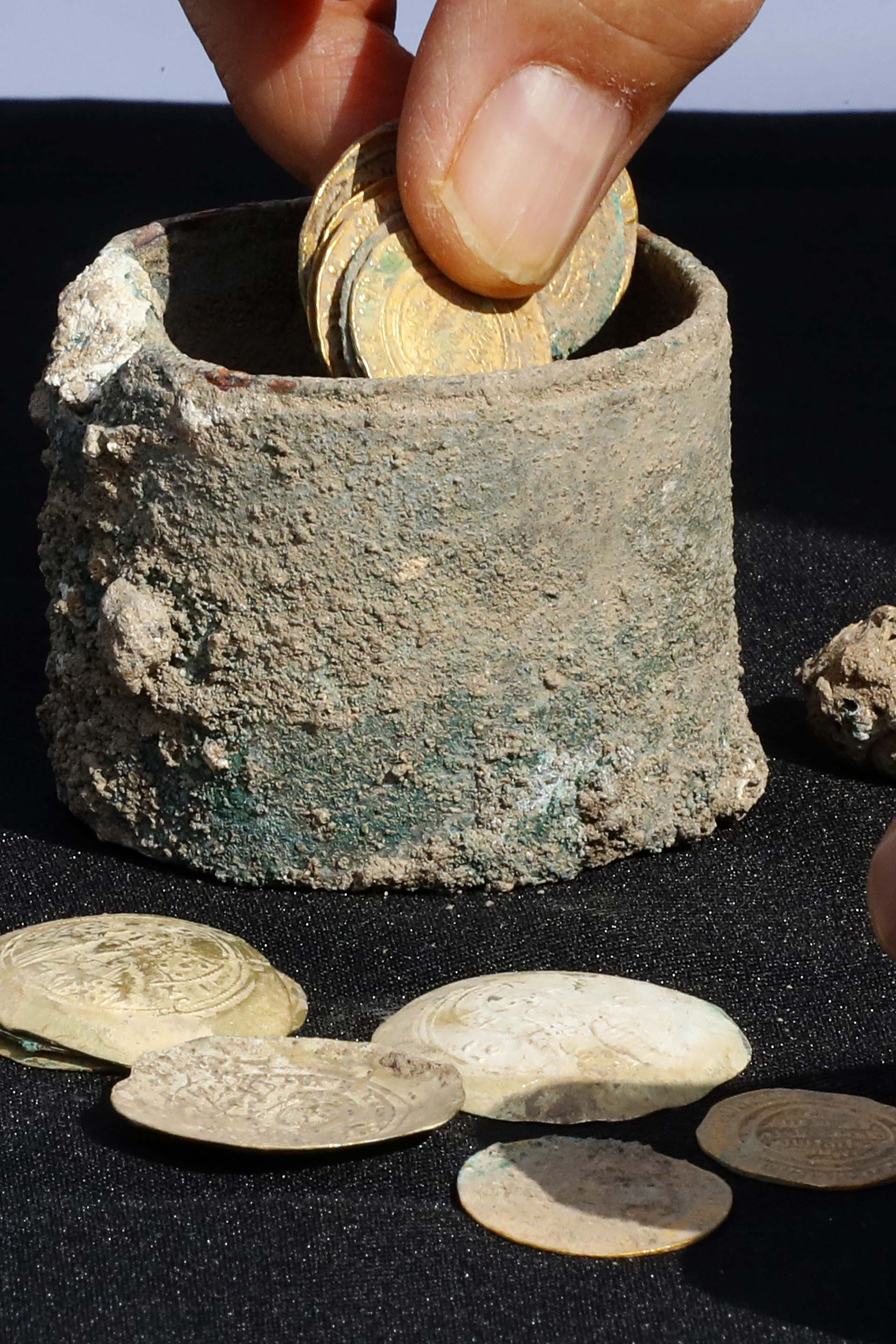 A picture taken on December 3, 2018, shows ancient gold coins and an earring recently uncovered at an excavation site in the Israeli Mediterranean town of Caesarea. – A treasure of 24 rare gold coins consisting of 18 Fatimid dinars, which were the standard local currency during that time (909-1171), as well as six are Byzantine coins, which include five dating to the era of Byzantine Emperor Michael VII Doukas (1071-1078), was recently uncovered in Caesarea. (Photo by JACK GUEZ / AFP)