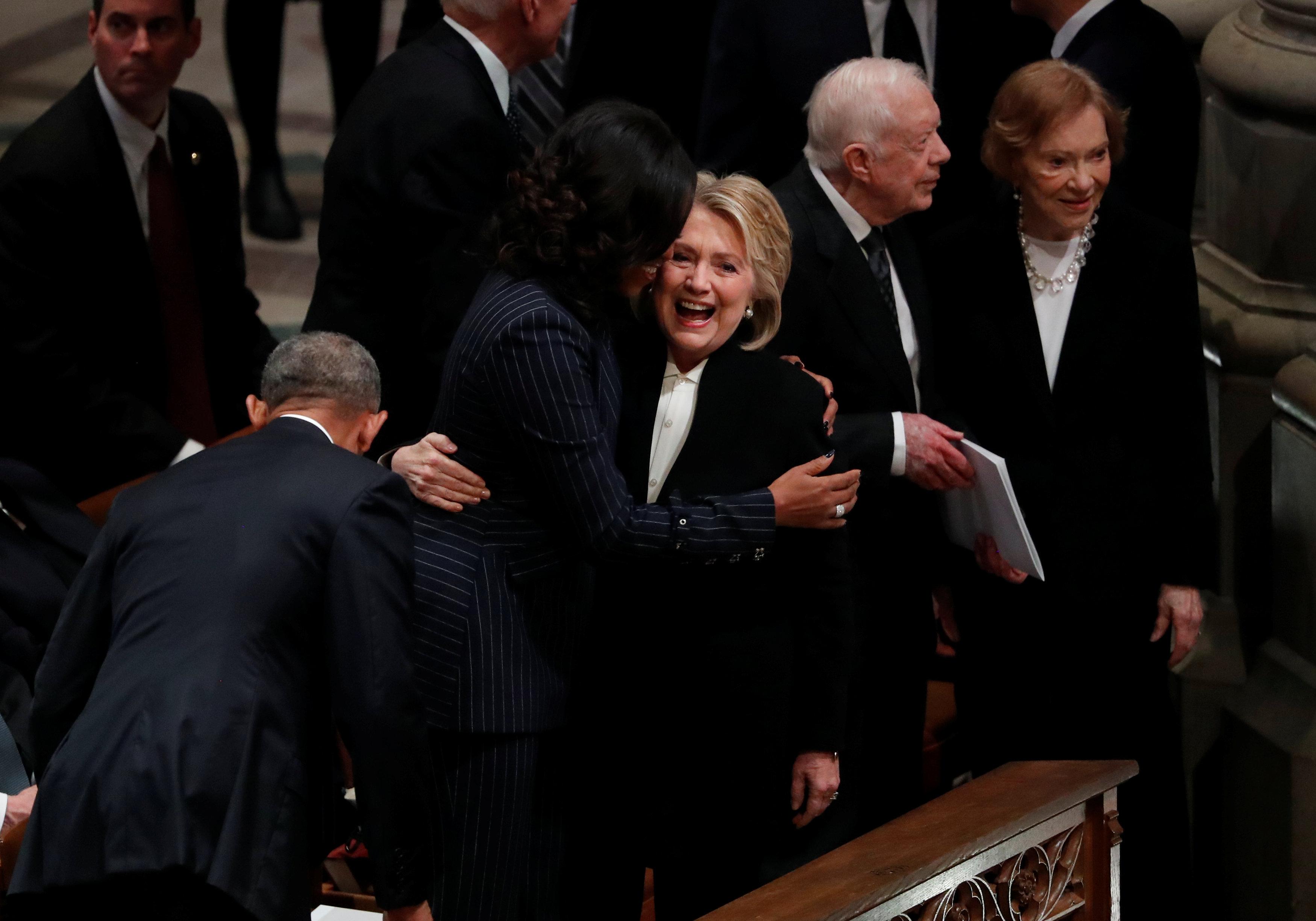La ex secretaria de Estado de Estados Unidos Hillary Clinton abraza a la ex primera dama Michelle Obama frente al ex presidente Jimmy Carter y a la ex primera dama Rosalynn Carter en el funeral de estado del ex presidente George H.W. Bush en la Catedral Nacional de Washington en Washington, Estados Unidos, el 5 de diciembre de 2018. (Reuters)