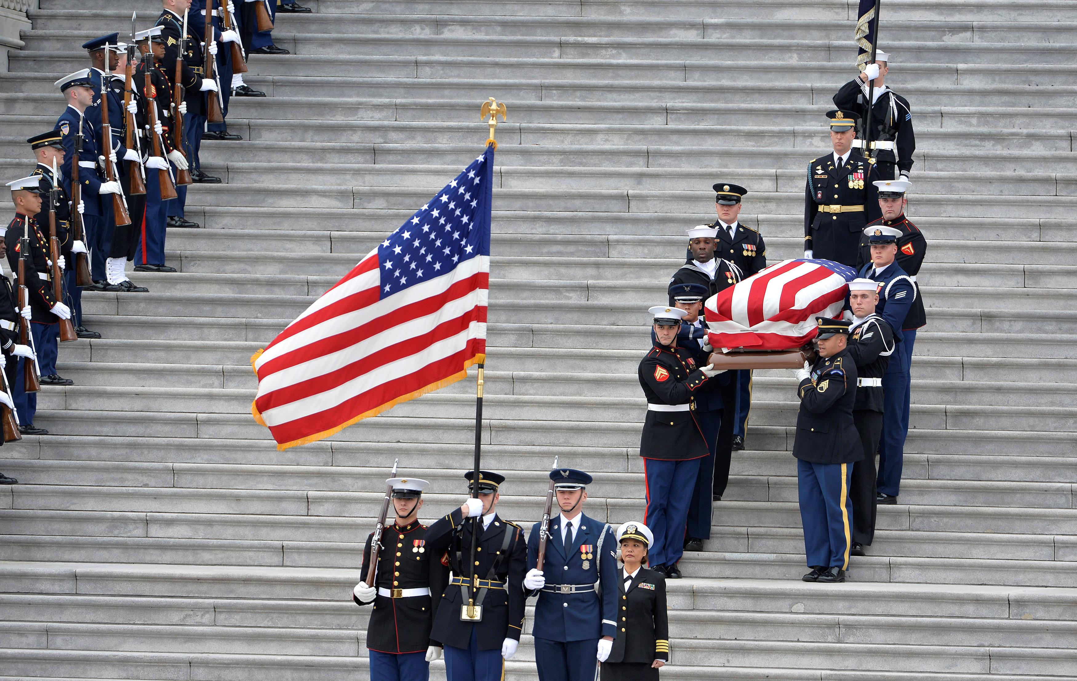 Una guardia de honor militar lleva el ataúd del difunto ex presidente George H.W. Bush a un coche fúnebre a la salida del Capitolio de Estados Unidos en dirección a la Catedral Nacional para los servicios funerarios, Washington, EE.UU., 5 de diciembre de 2018. (Reuters)