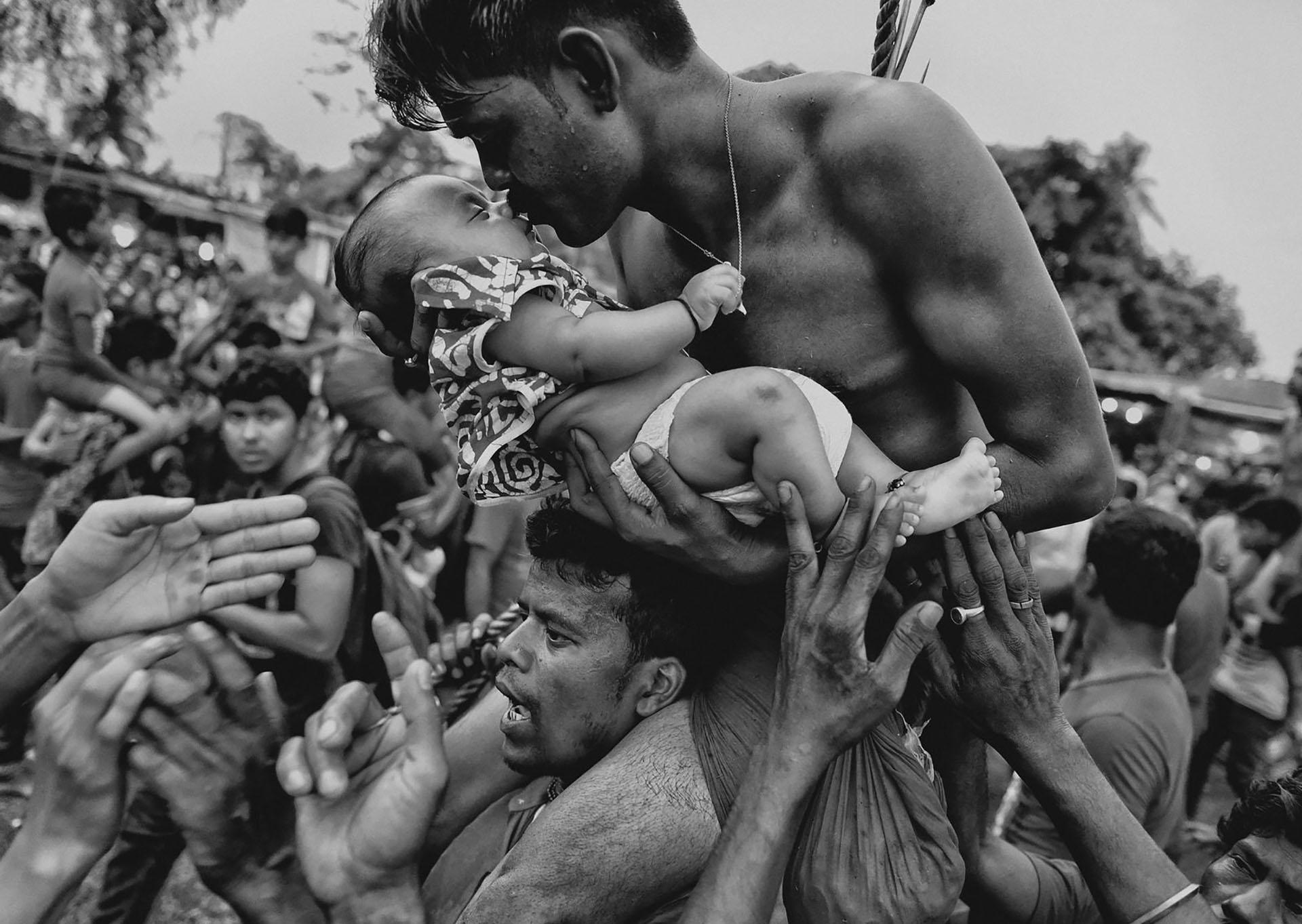 Un hombre hindú besa a un recién nacido durante el festival Charak Puja, en la India