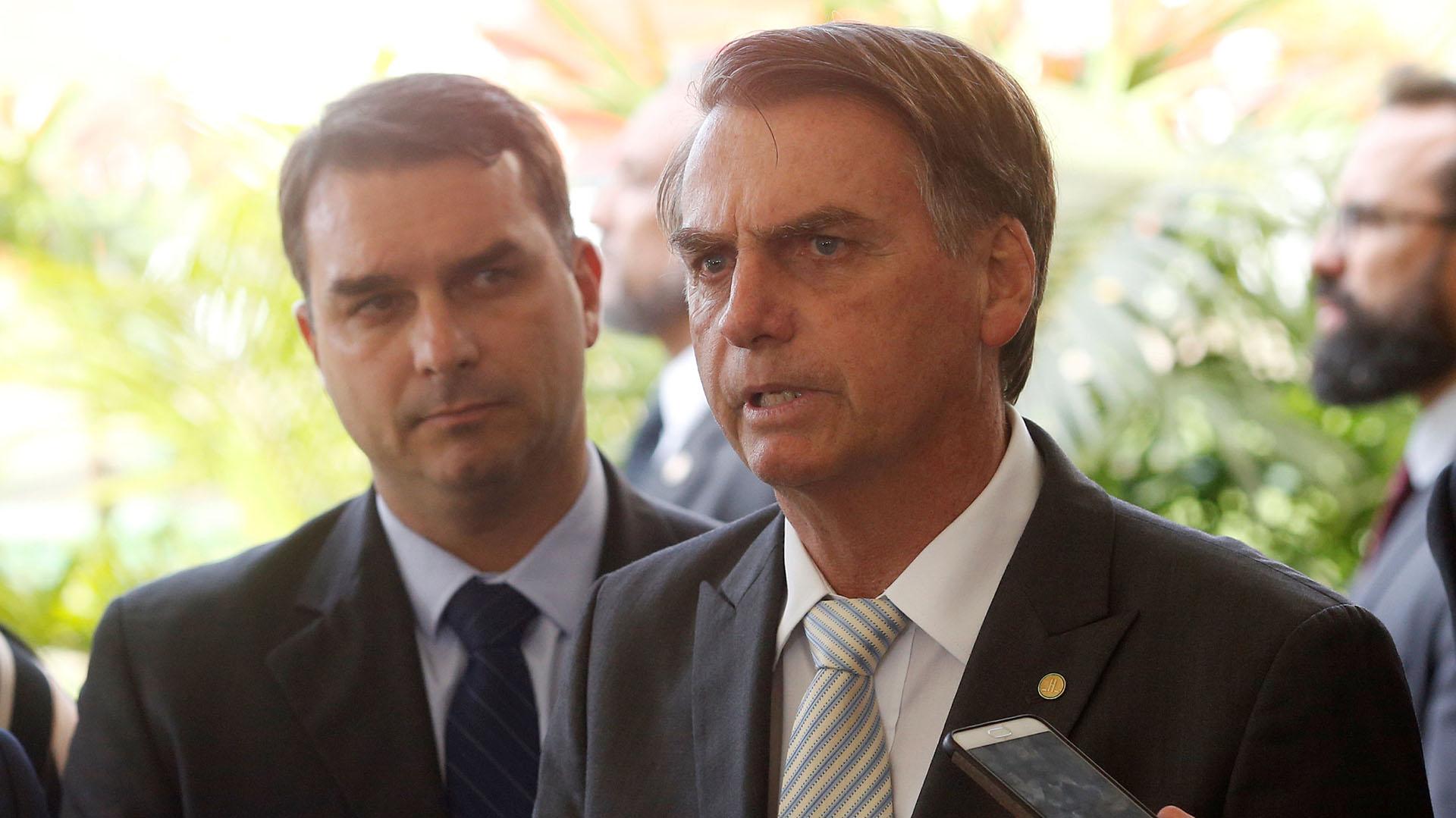 Jair Bolsonaro habla a la prensa y detrás suyo está su hijo Flavio, involucrado en una denuncia de corrupción a partir de fondos que movilizó su ex chofer.