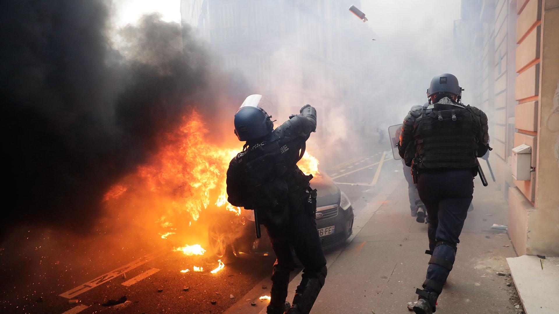 Dos policías responden ante el avance de los manifestantes (AFP)