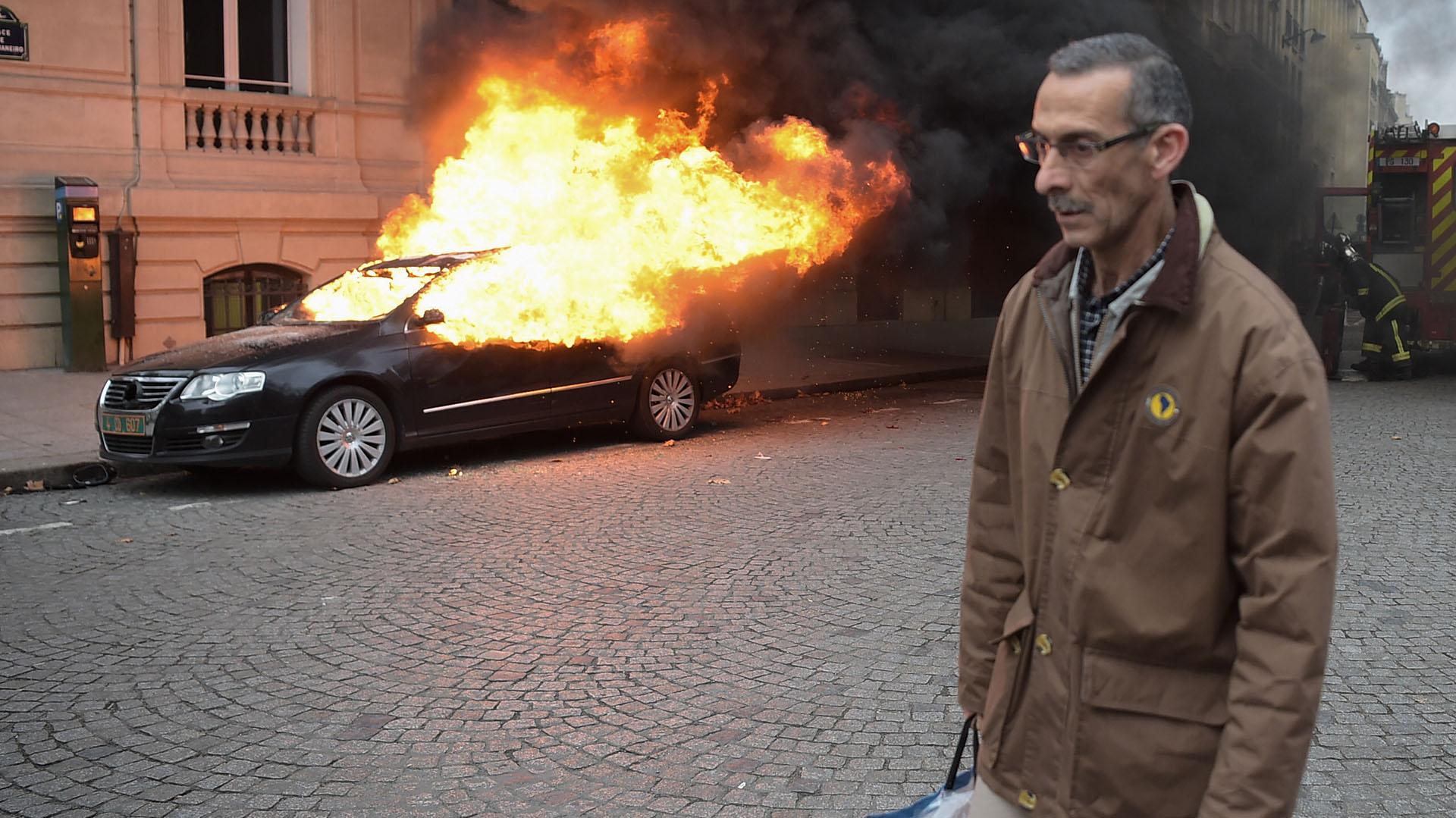 Un hombre camina entre los vehículos prendidos fuego (AFP)