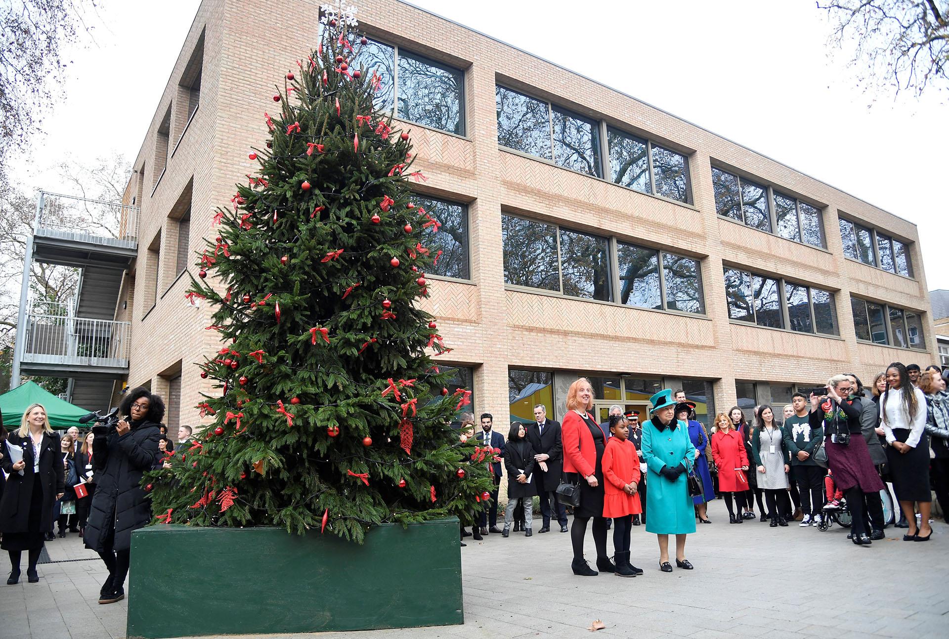 LONDRES, GRAN BRETAÑA. La reina británica Elizabeth, Shylah Gordon y Coram, CEO Carol Homden junto al árbol de navidad de caridad en Londres