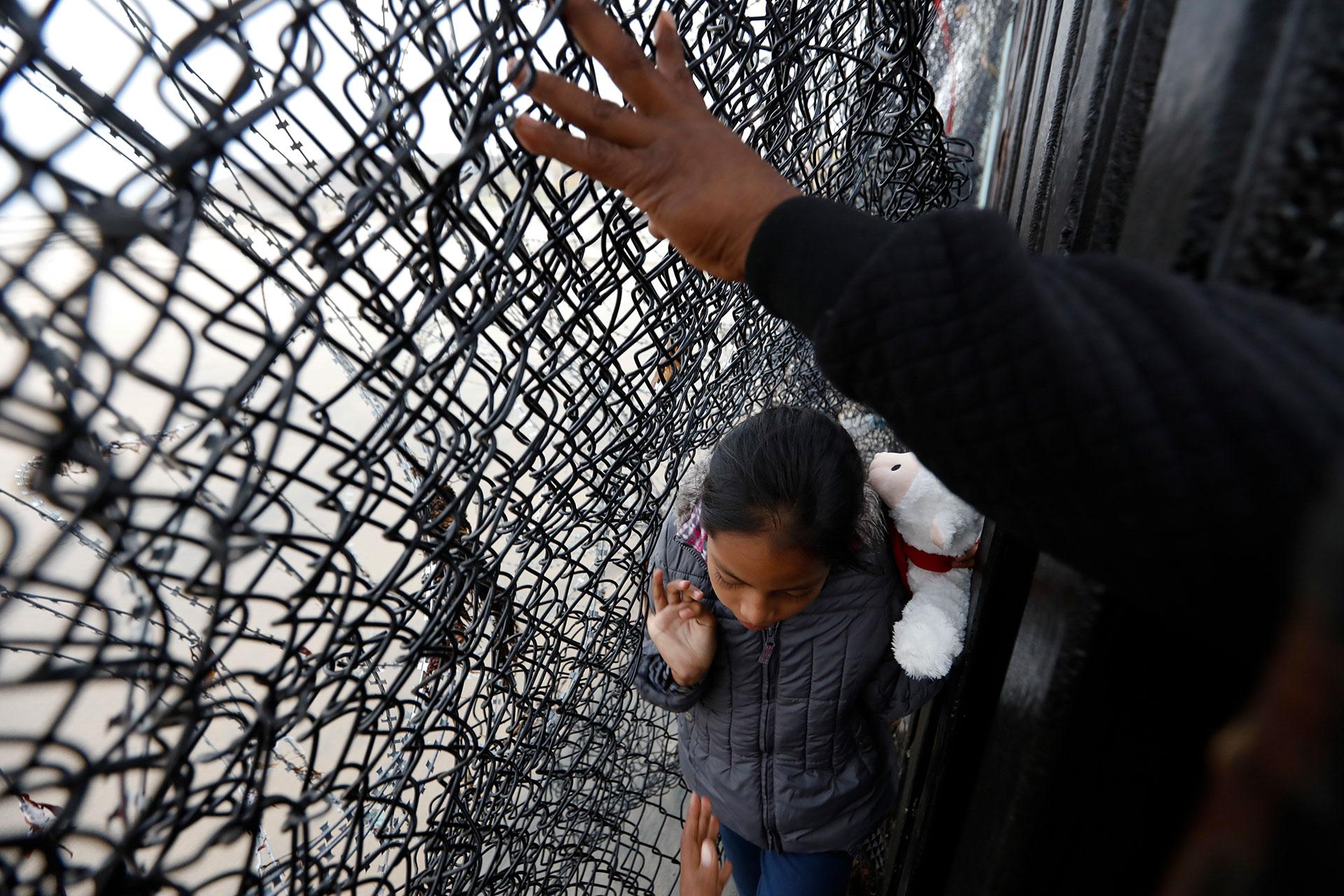 Una niña ayudada por su familia busca un hueco en el enrejado para cruzar a territorio estadounidense