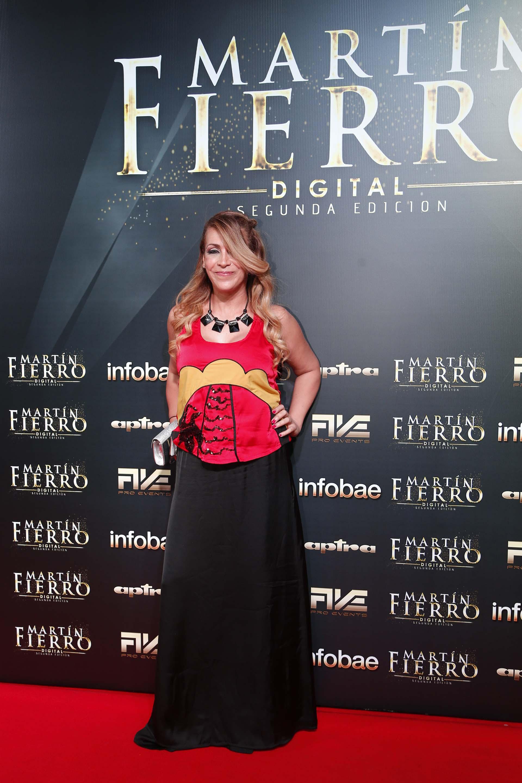 La periodista Alejandra Rubio, lució un conjunto de dos piezas: blusa colorada con bordados y detalles de dorado, y falda negra. Completó su look con collar de acrílico y sobre plateado