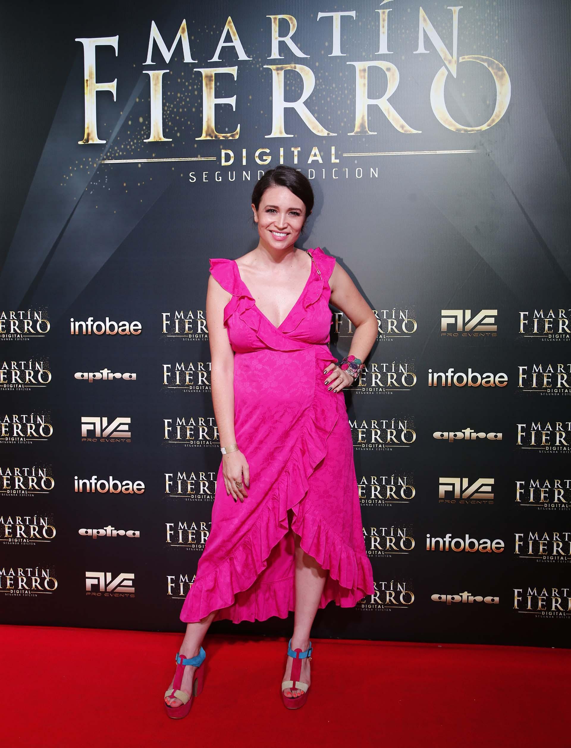 Julia Mengolini. La conductora eligió un vestido de corte irregular con volados en fucsia. Acompañó el look con sandalias a tono, y brazalete multicolor rígido