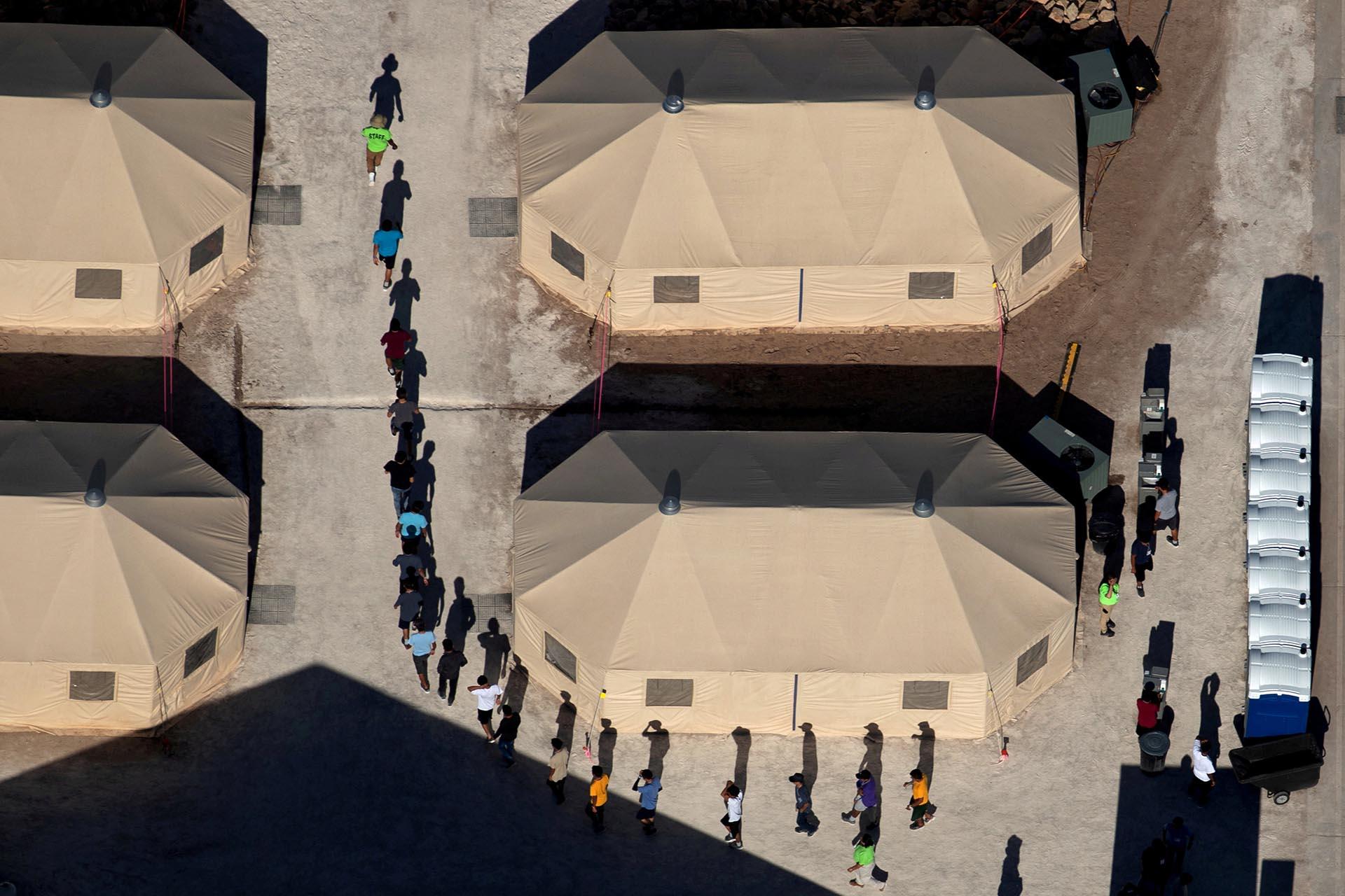 Niños inmigrantes separados de sus padres, tras ser capturados intentando entrar ilegalmente en Estados Unidos, caminan en un campo ubicado en Tornillo, Texas, cerca de la frontera con México, el 18 de junio (Reuters)