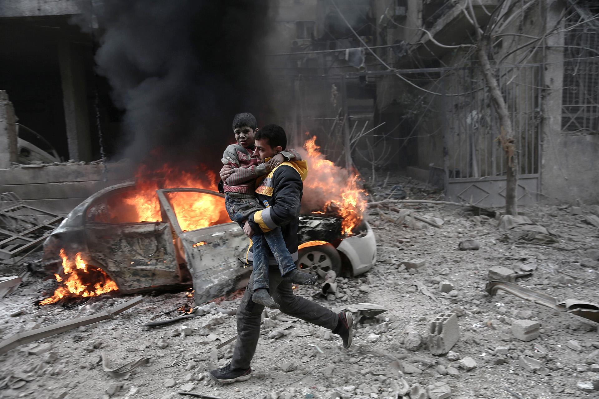 Un paramédico sirio carga a un niño herido tras un bombardeo de la Fuerza Aérea Siria en Guta Oriental el 6 de enero de 2018 (ABDULMONAM EASSA / AFP)