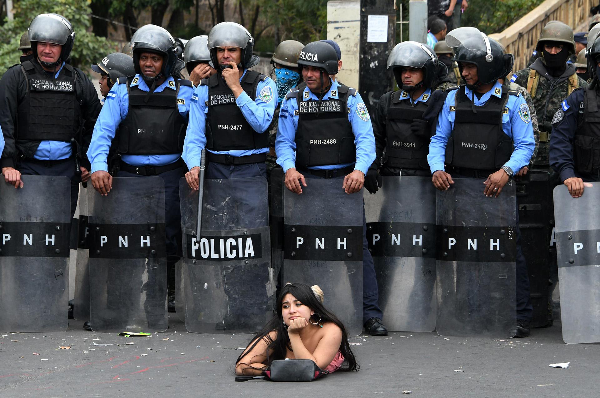 Una seguidora de Salvador Nasralla, candidato presidencial de la opositora Alianza Contra la Dictadura se acuesta en la calle, delante de oficiales de la Policía de Honduras durante una protesta contra la reelección de Juan Orlando Hernandez, el 21 de enero en Tegucigalpa (Orlando SIERRA / AFP)