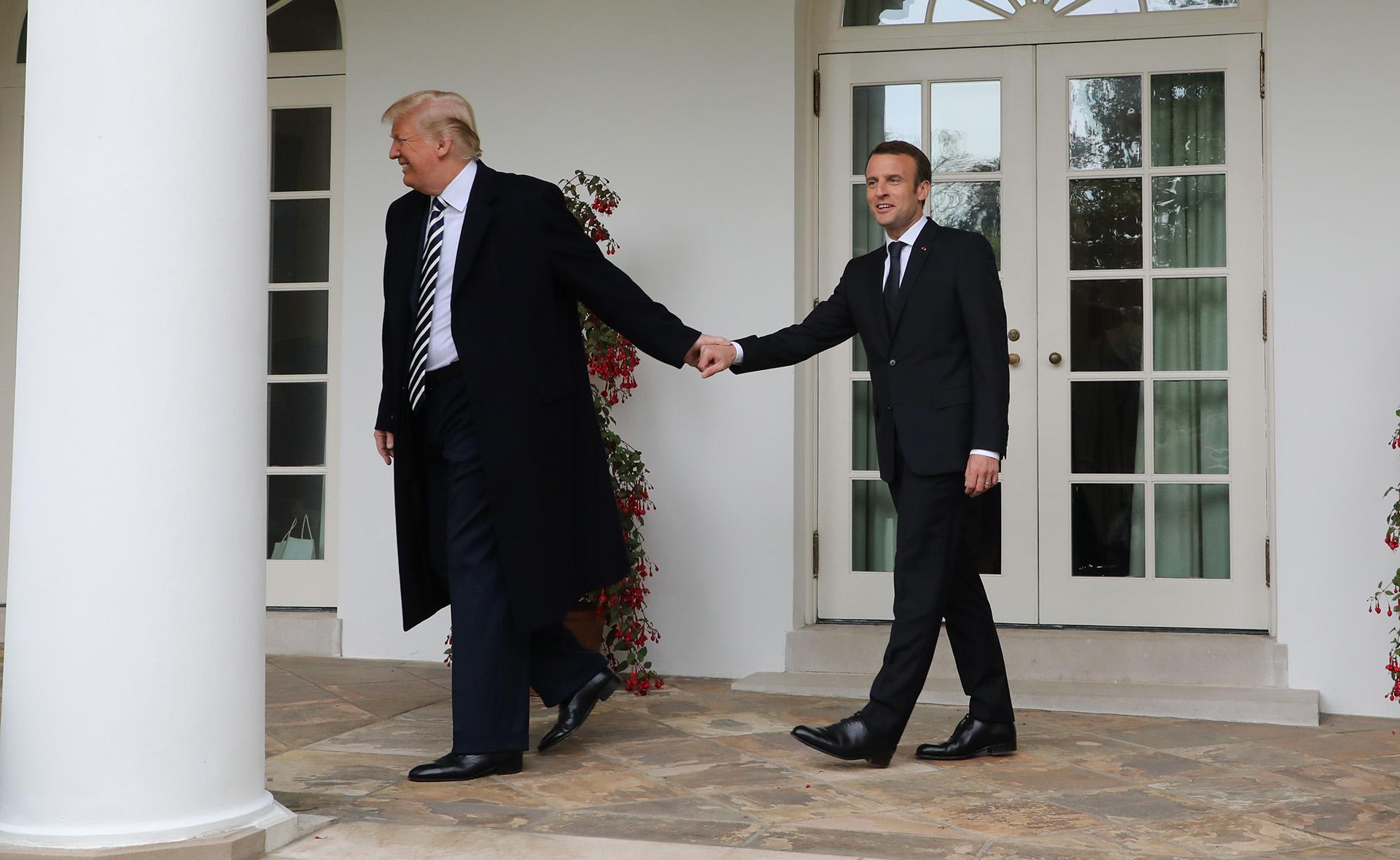 El presidente estadounidense Donald Trump lleva de la mano a su par francés Emmanuel Macron durante una visita oficial en la Casa Blanca, el24 de abril (Ludovic MARIN / AFP)