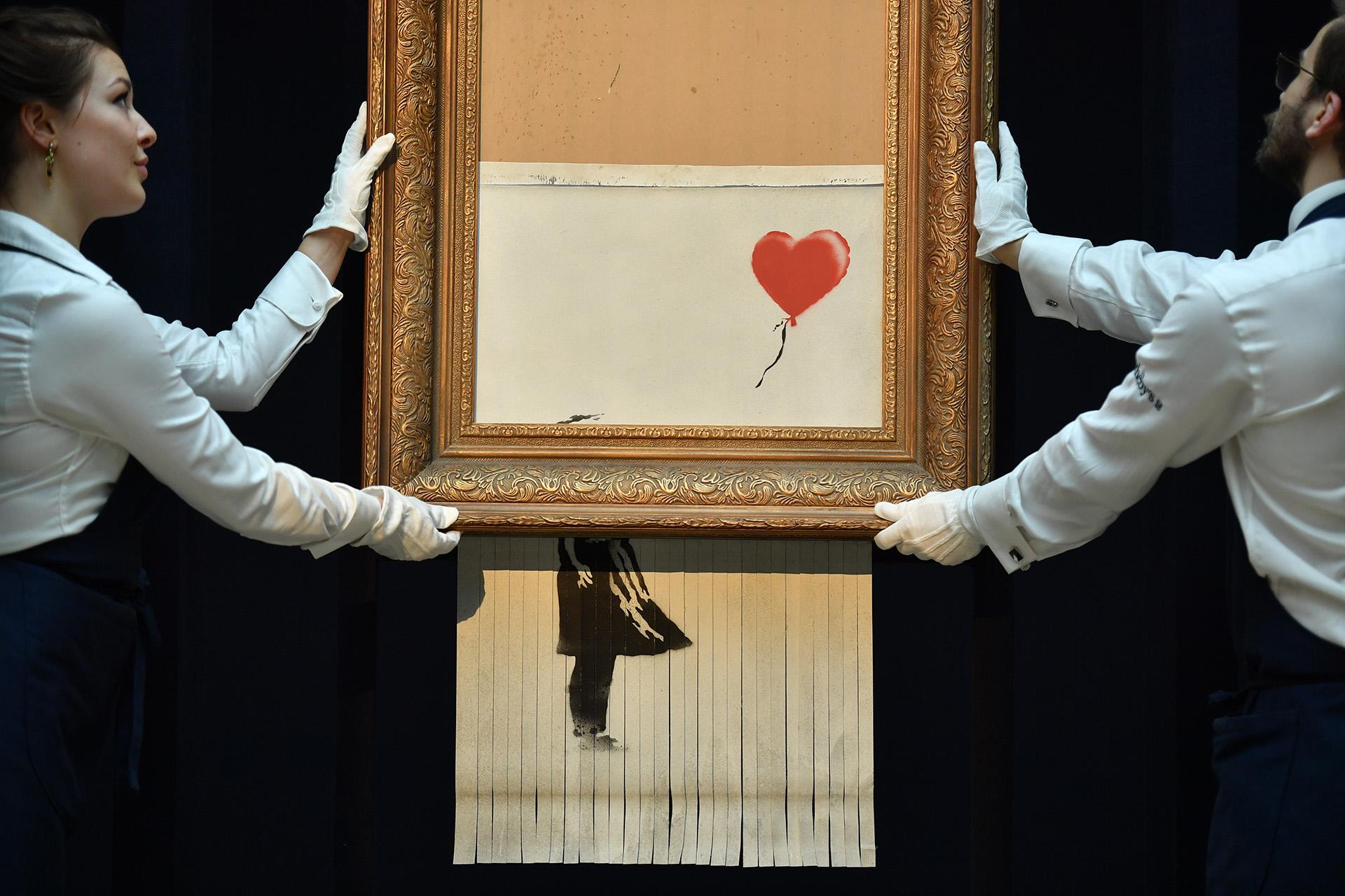 """Empleados de Sotheby sostienen el cuadro de Banksy titulado """"El amor es en el tacho"""", mientras este se autodestruyeel12 de octubre en Londres (Ben STANSALL / AFP)"""